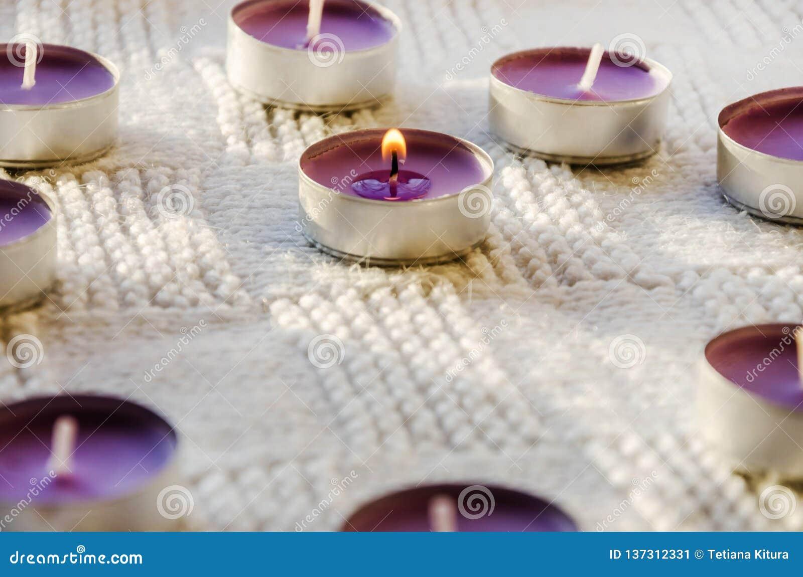 Petites, pourpres, aromatiques bougies sur un fond blanc