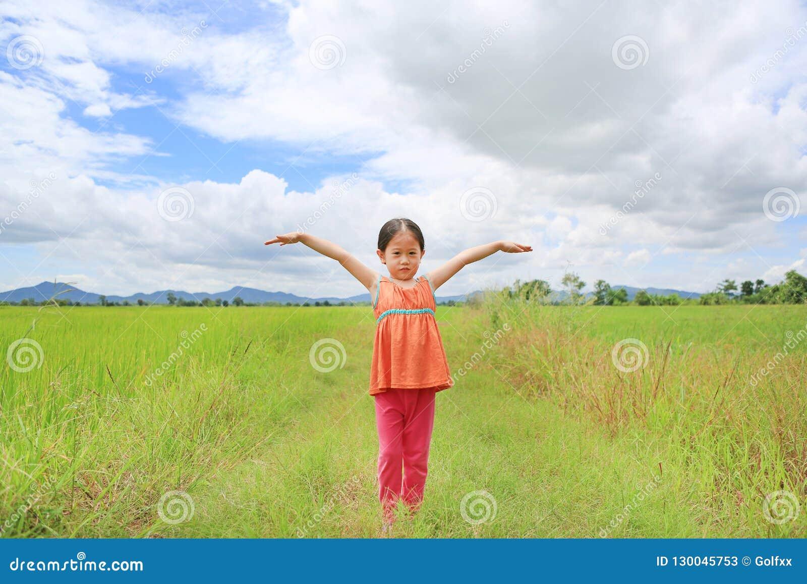 Petits bras asiatiques adorables de bout droit de fille d enfant et détendu aux jeunes rizières vertes avec le ciel de montagne e