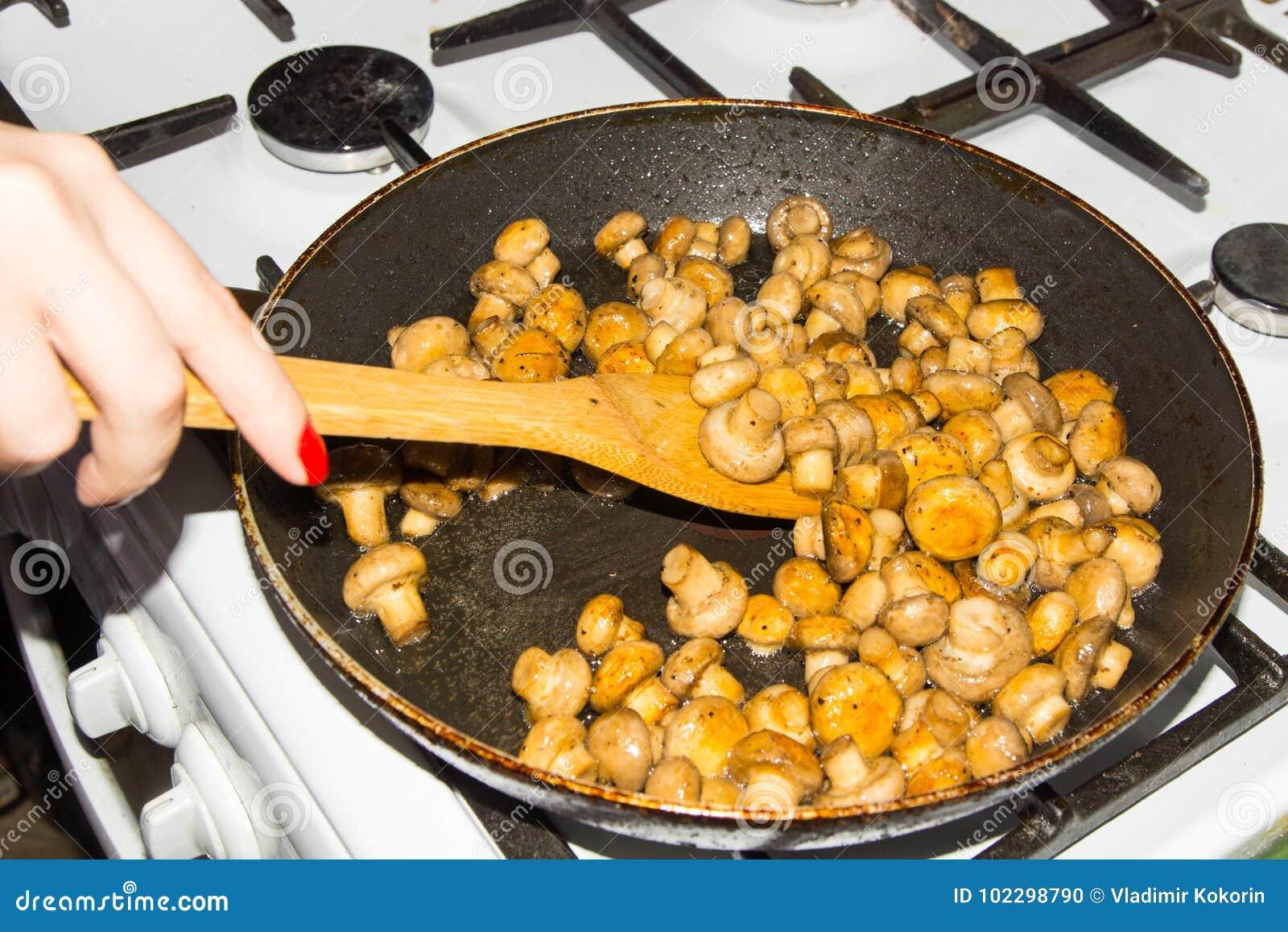 Petits champignons frits dans une casserole dans son ensemble Champignons frits aux oignons