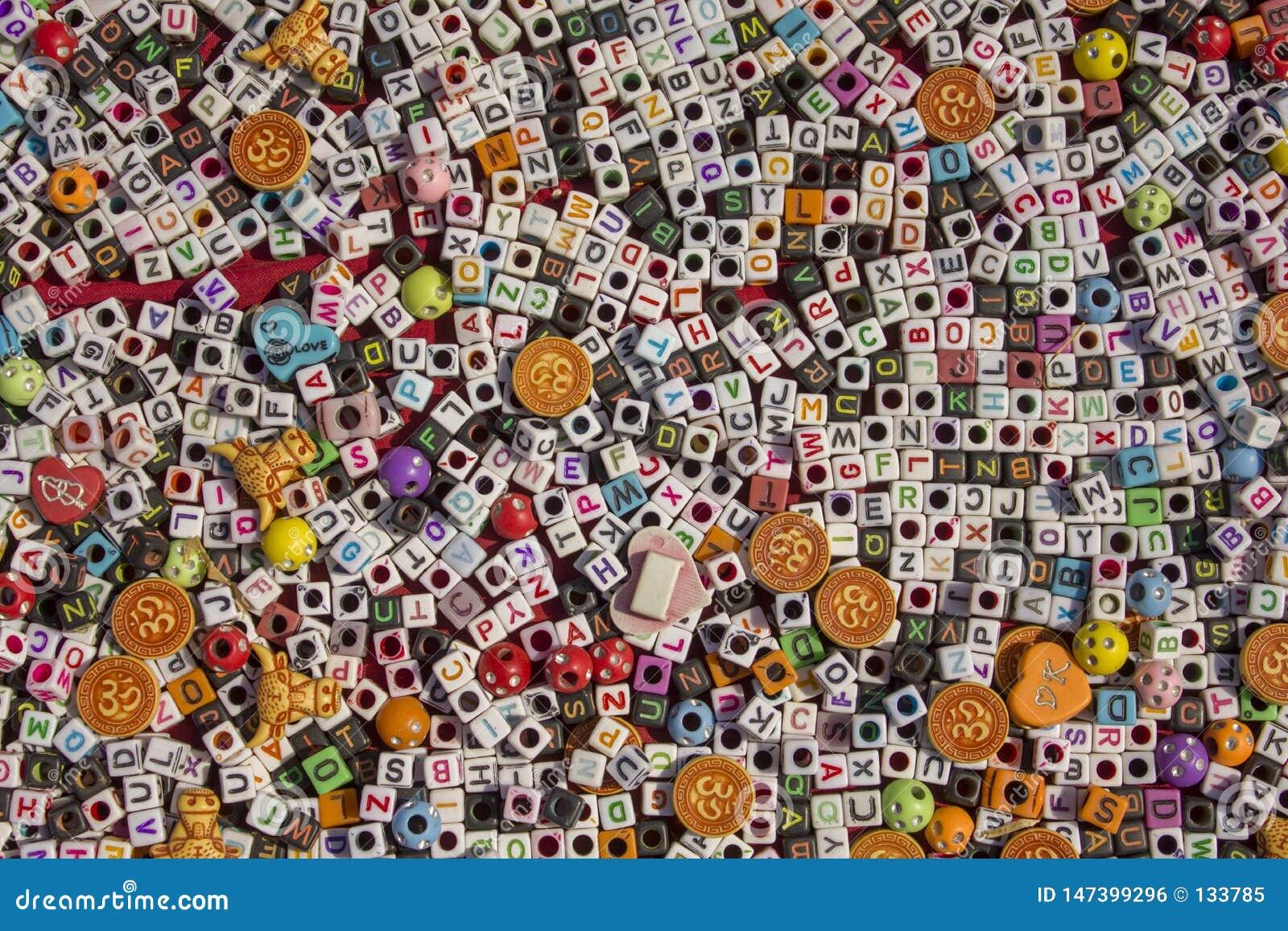 Petits cubes blancs et noirs avec des trous et le mensonge d alphabet anglais sur la surface rouge du plan rapproché de table, le