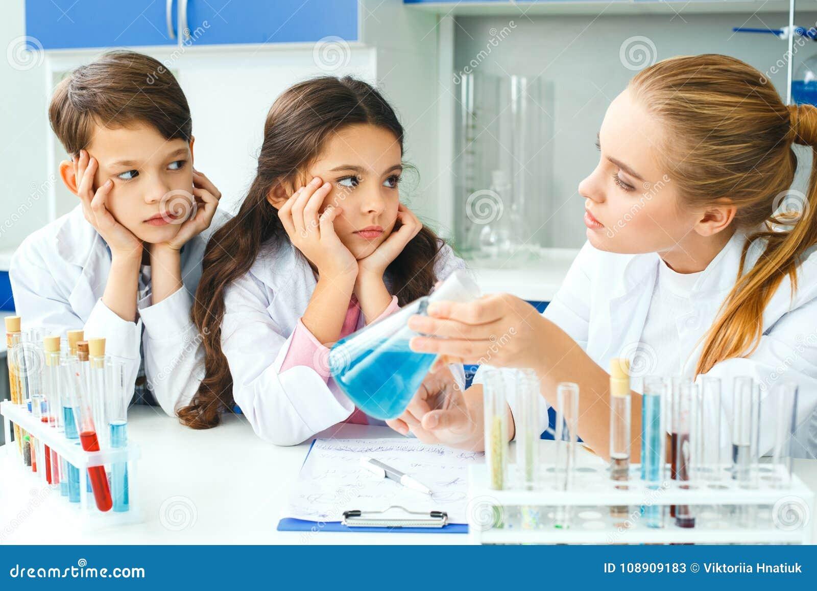 Petits enfants avec le professeur dans la leçon d explainig de laboratoire d école