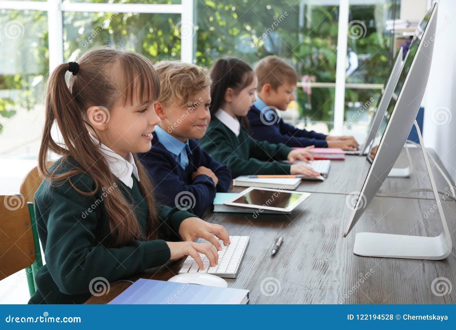 Petits enfants dans l uniforme scolaire élégant aux bureaux