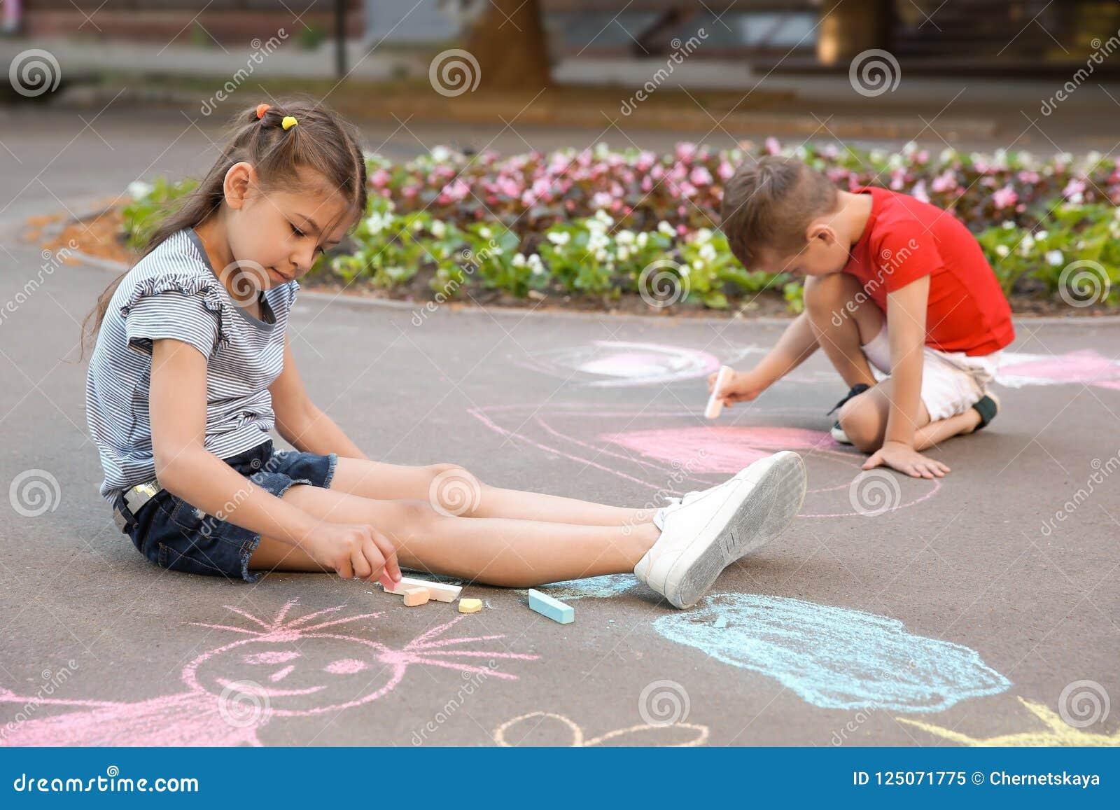 Petits enfants dessinant avec la craie colorée