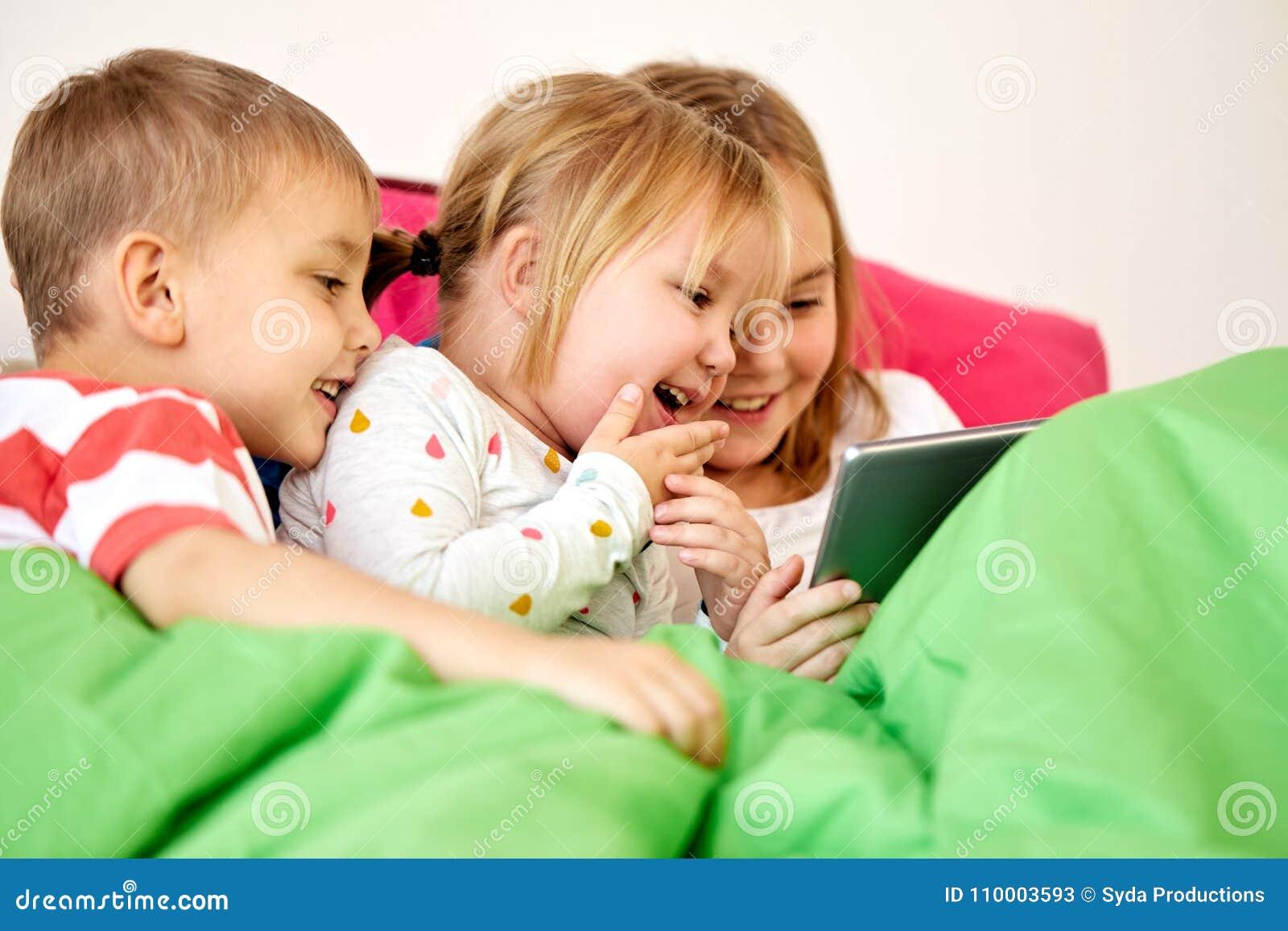 Petits enfants heureux avec le PC de comprimé dans le lit à la maison