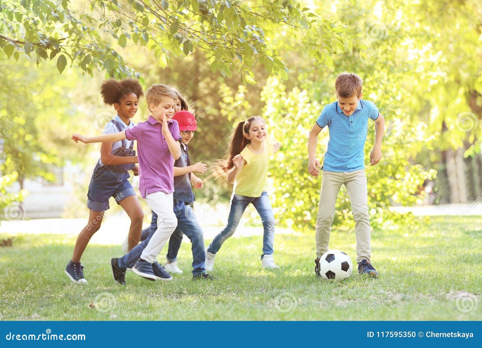 Petits enfants mignons jouant avec la boule dehors