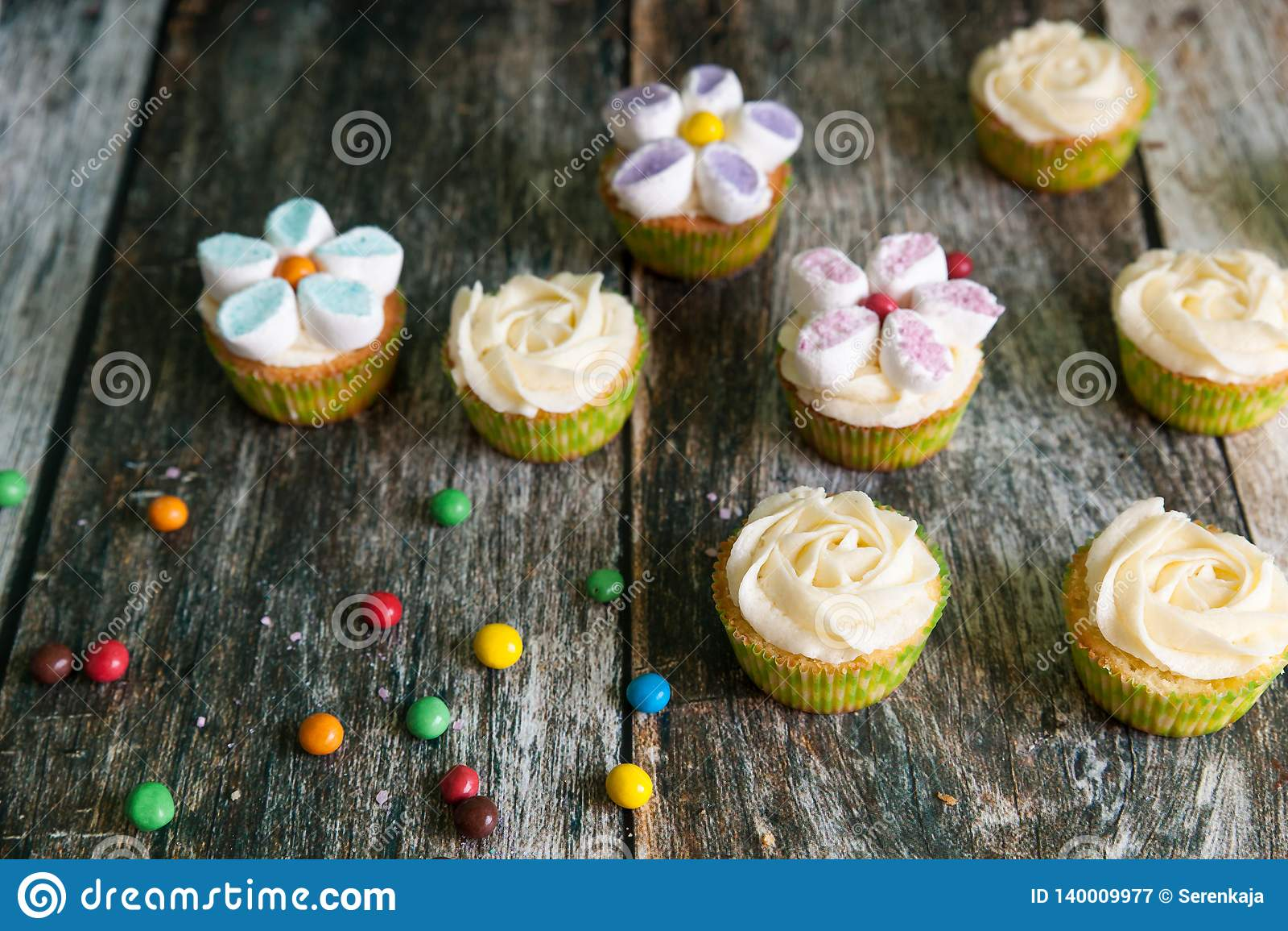 Petits gâteaux décorés des fleurs de crème et de guimauve de beurre