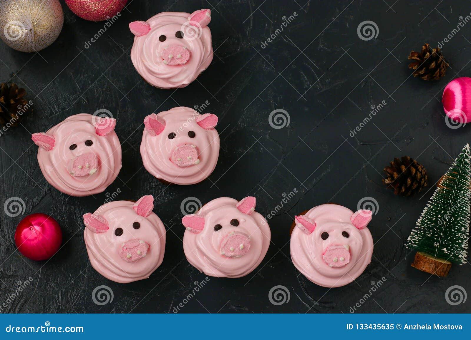 Petits gâteaux roses de porc - les petits gâteaux faits maison décorés de la crème et de la guimauve de protéine ont formé les pi