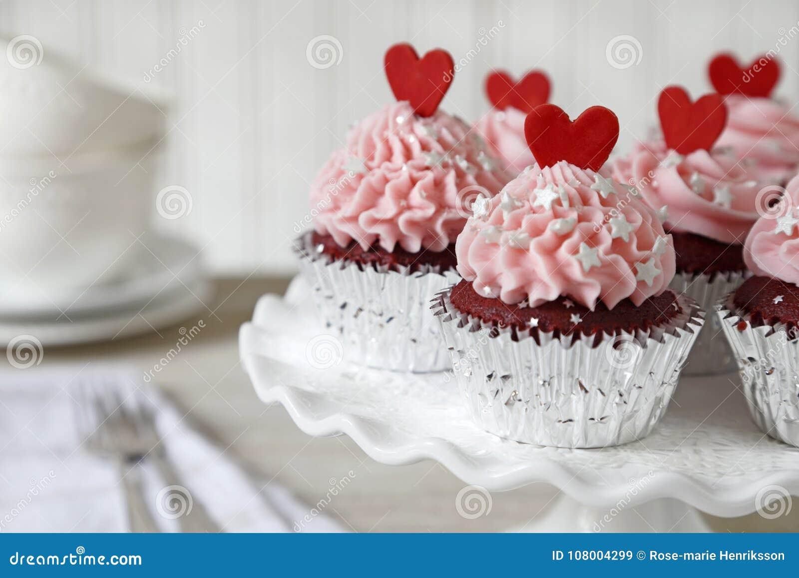 Petits gâteaux rouges de velours avec les coeurs rouges