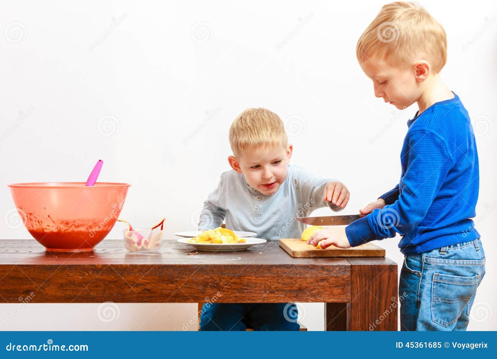 Petits garçons coupant la pomme avec un couteau de cuisine