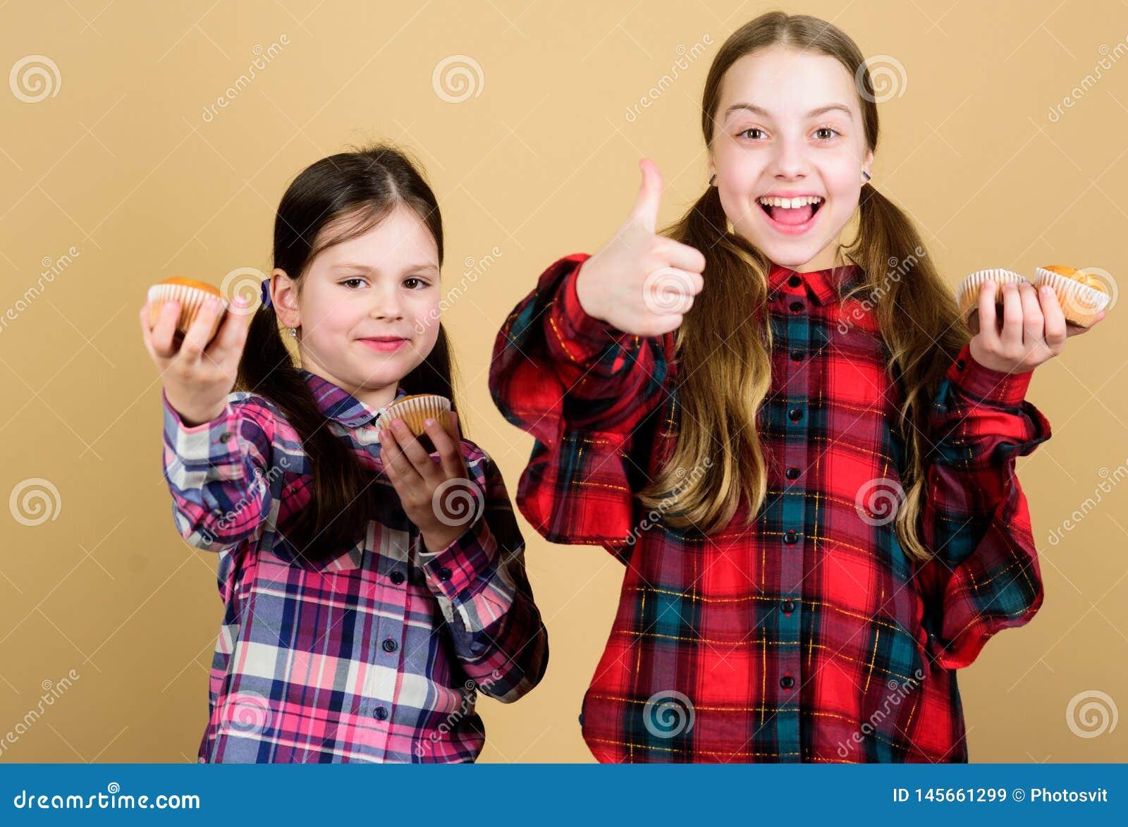 Petits pains d?licieux Enfants mignons de filles mangeant les petits pains ou le petit g?teau Dessert doux Recette culinaire Cass