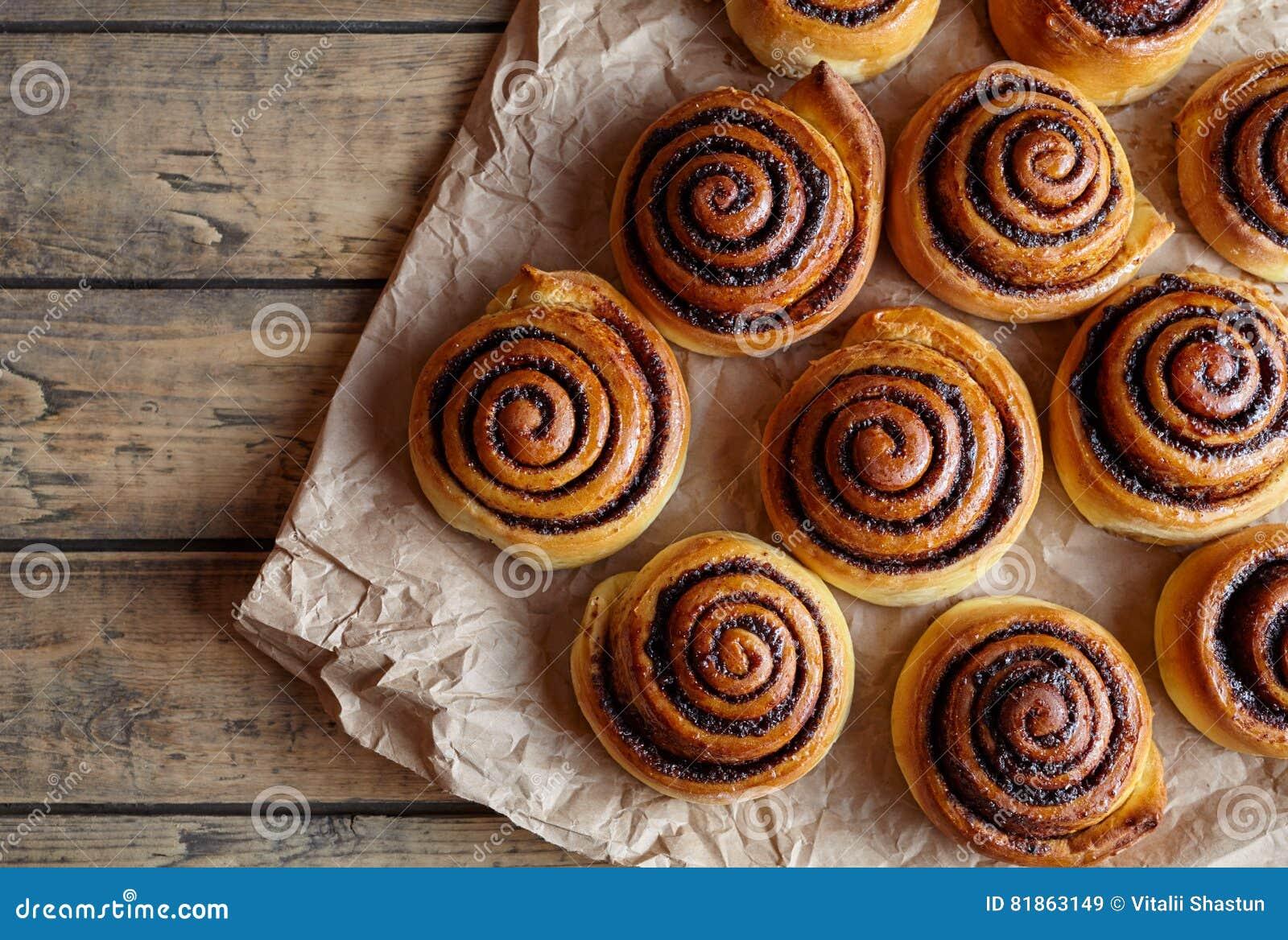 Petits pains de cannelle fraîchement cuits au four avec les épices et le cacao remplissant sur le papier parcheminé Cuisson faite