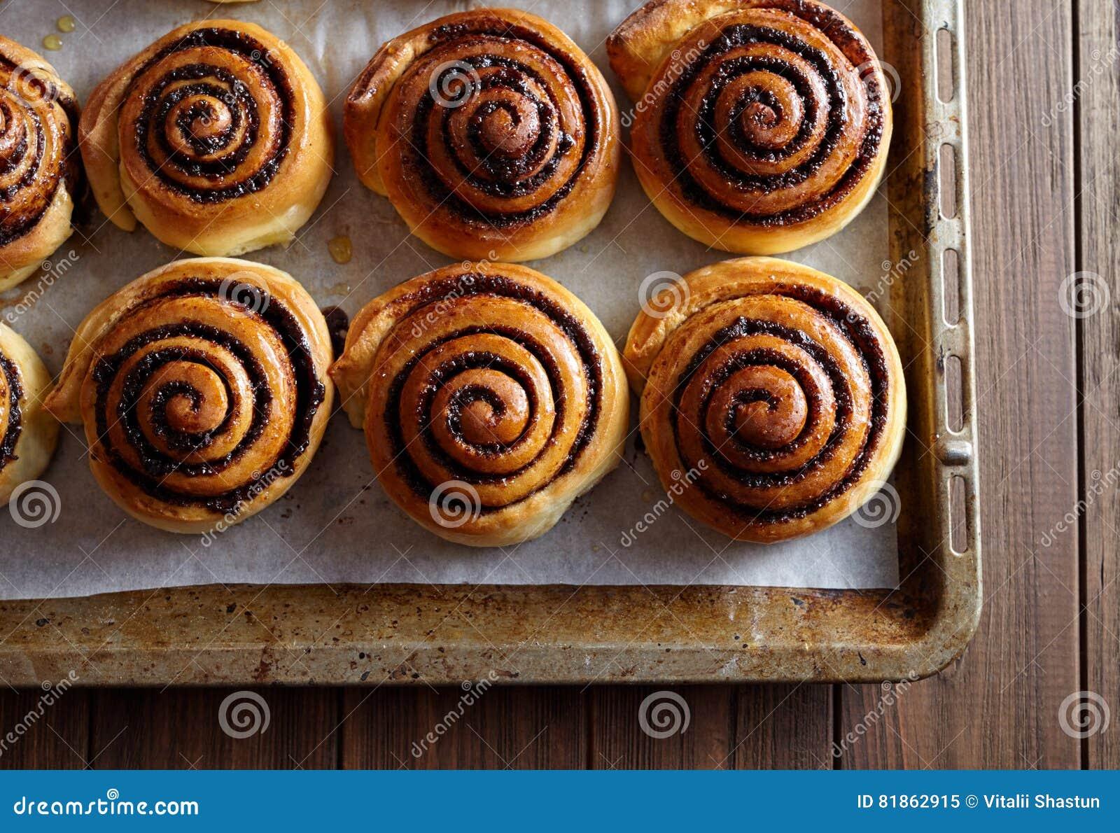 Petits pains fraîchement cuits au four de petits pains de cannelle avec du cacao et des épices sur une plaque de cuisson en métal