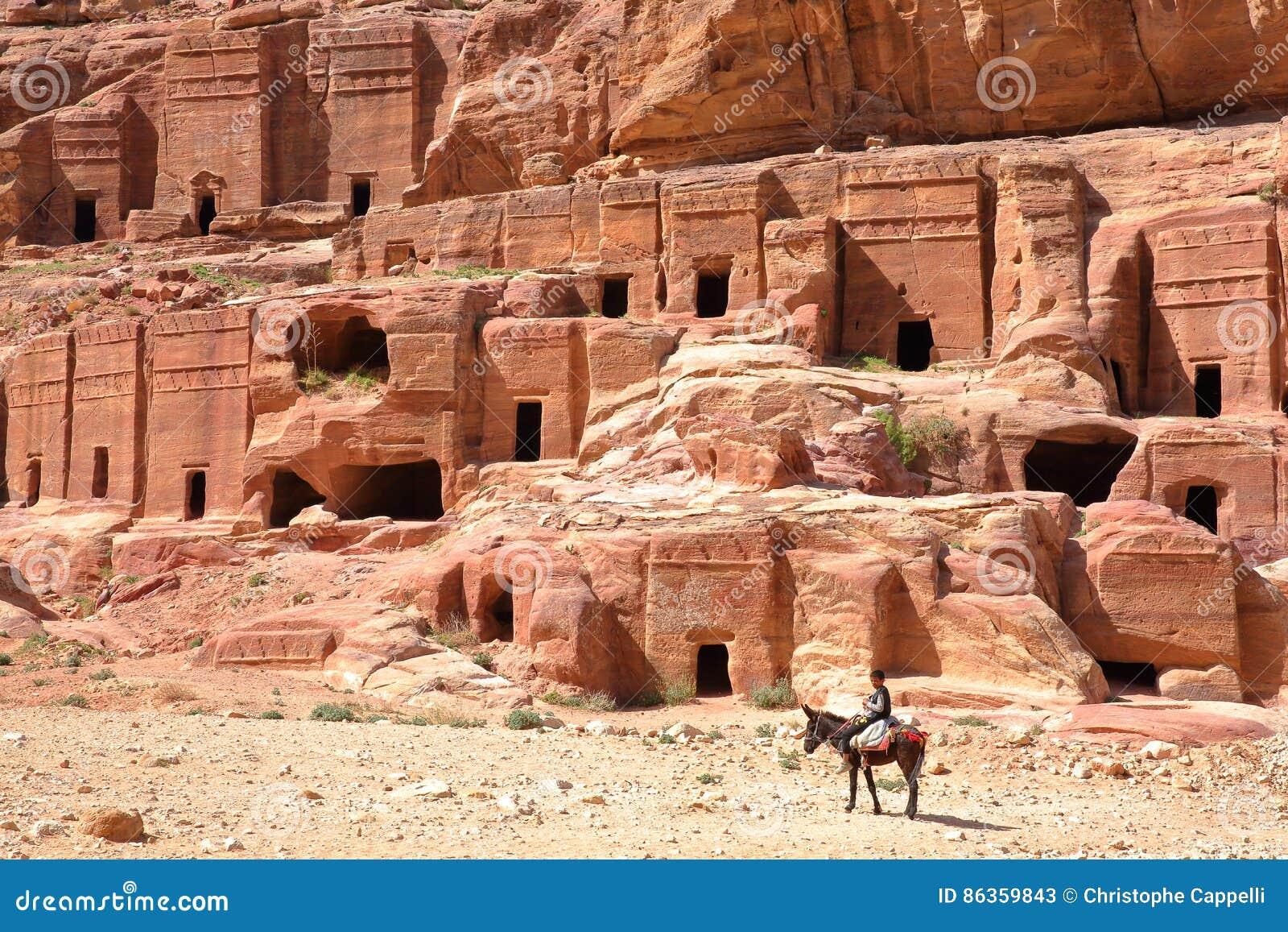 PETRA, JORDANIEN - 11. MÄRZ 2016: Die Straße von Fassaden mit einem kleinen beduinischen Jungen, der seinen Esel im Vordergrund r