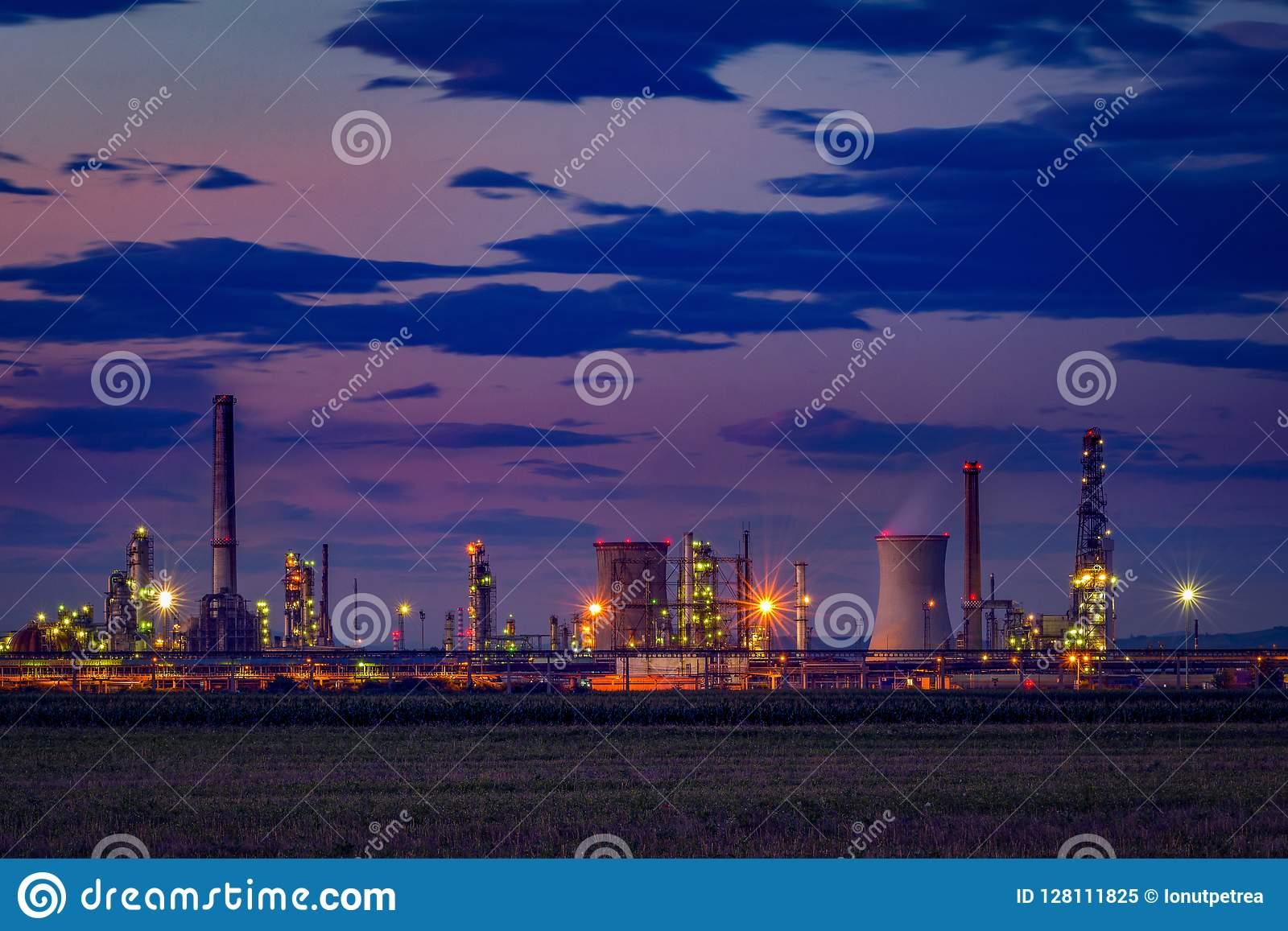 Petrol oil refinery located near a cultivated field at dusk