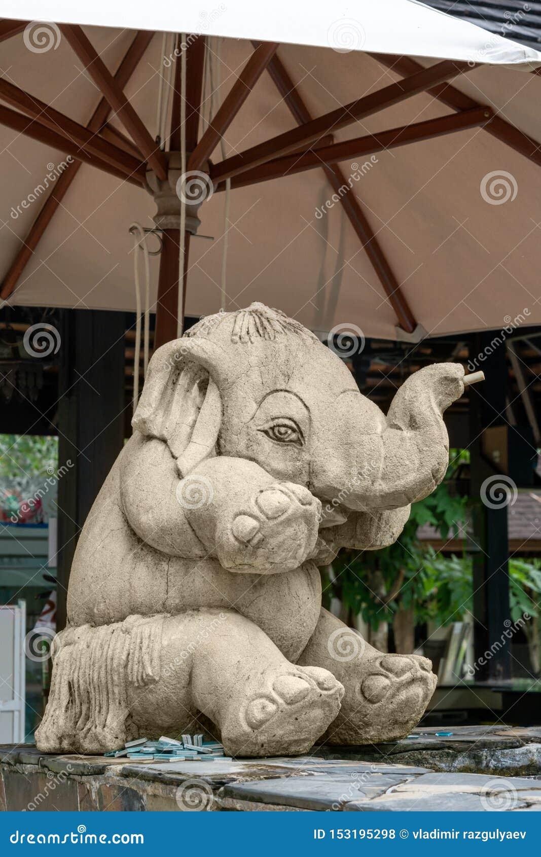 Peu éléphant drôle, sculpture, se reposant sous un parapluie