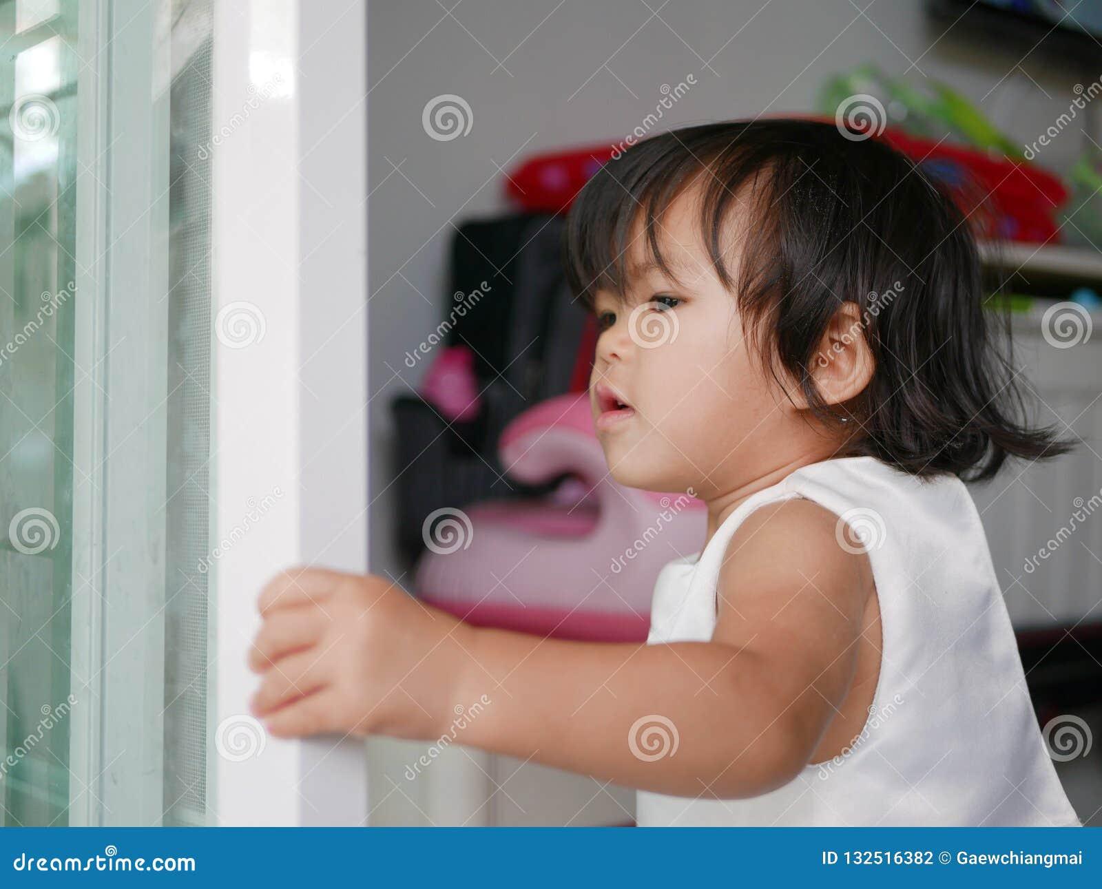 Peu bébé asiatique apprenant à fermer/porte coulissante étroite seule