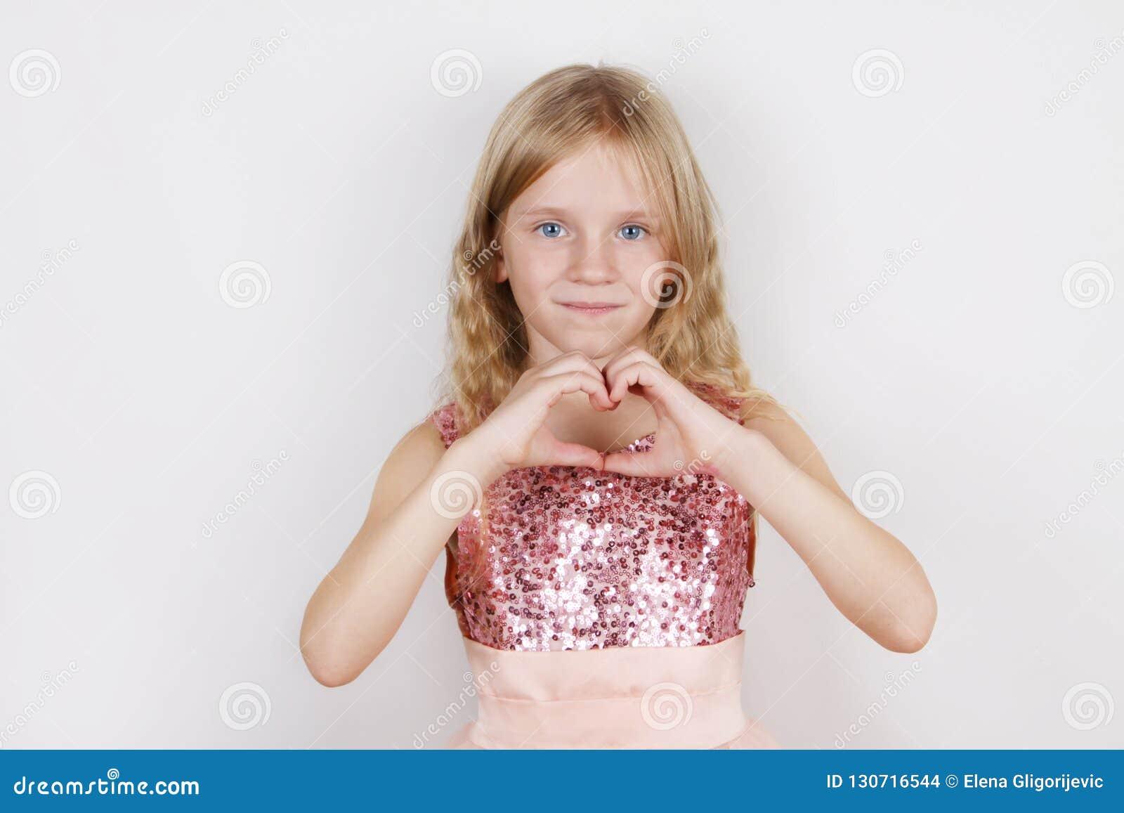 Peu belle fille blonde faisant la forme de coeur avec des mains