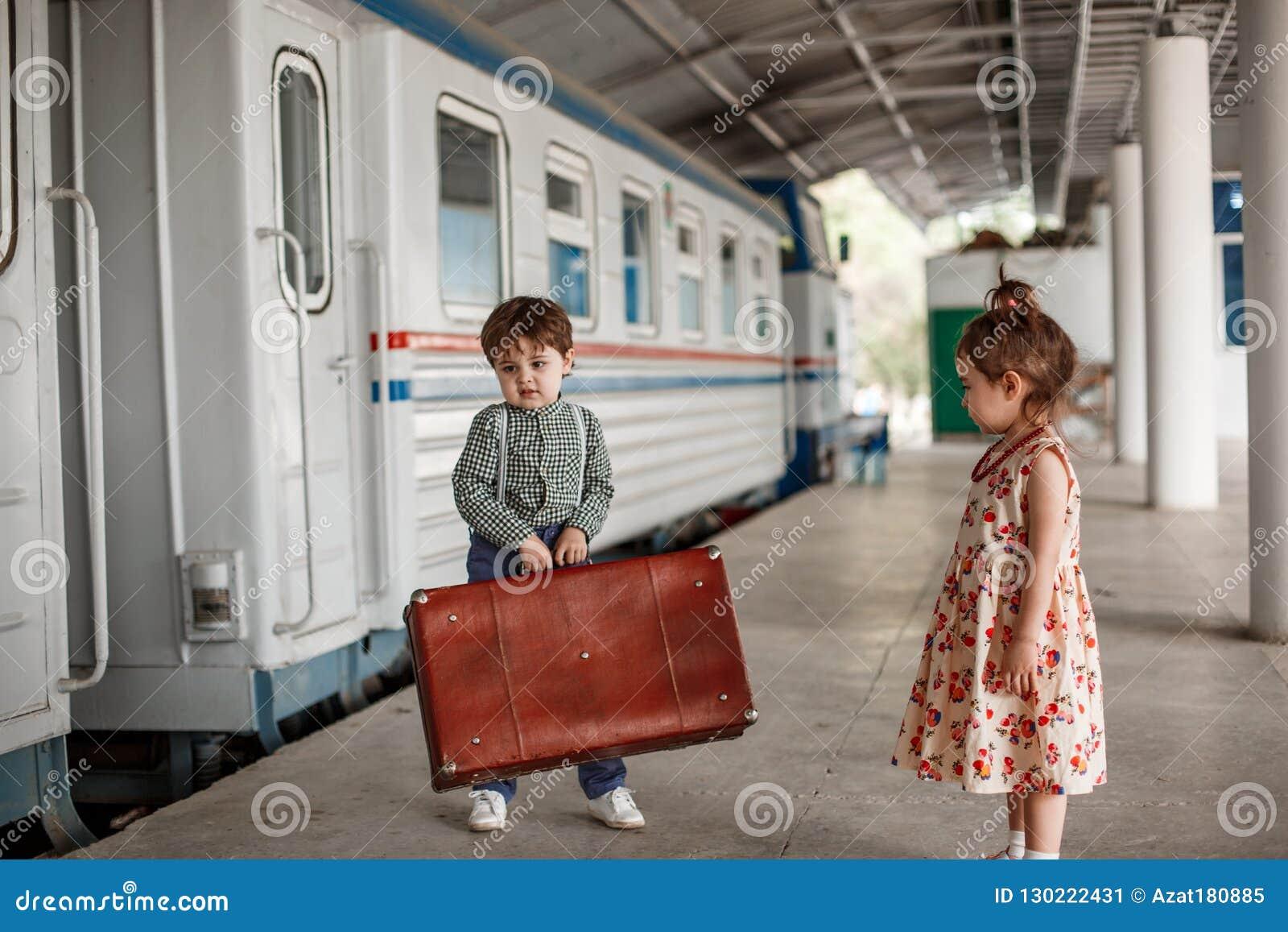 Peu belle fille dans la rétro robe indique au revoir à la station avec un petit garçon dans des vêtements de cru avec la rétro va