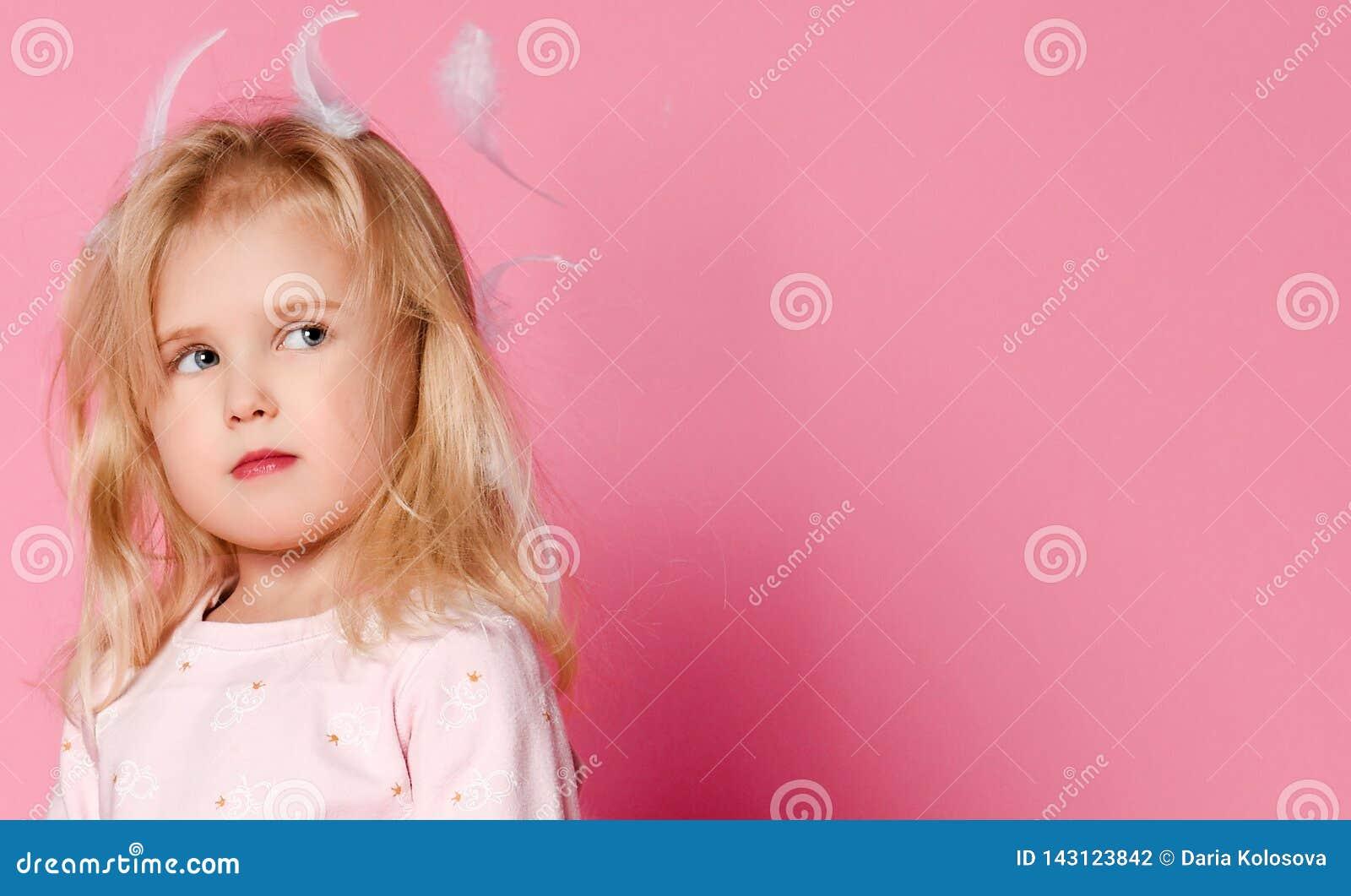 Peu blonde de fille avec des plumes dans ses cheveux