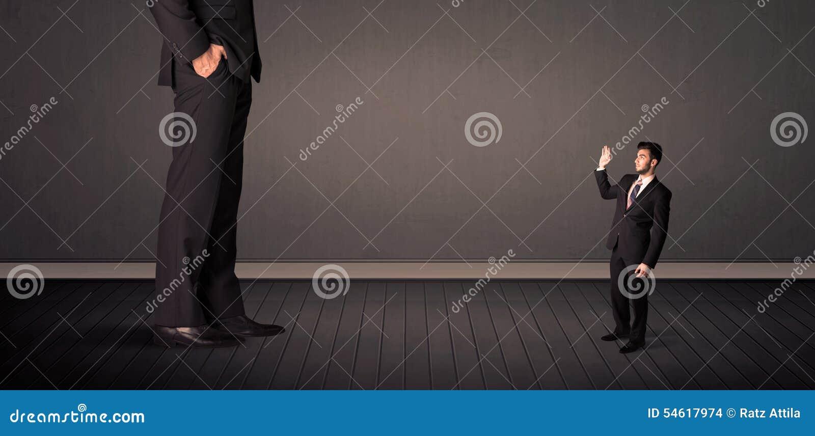 Peu de bussinesman devant un concept de jambes de patron de géant