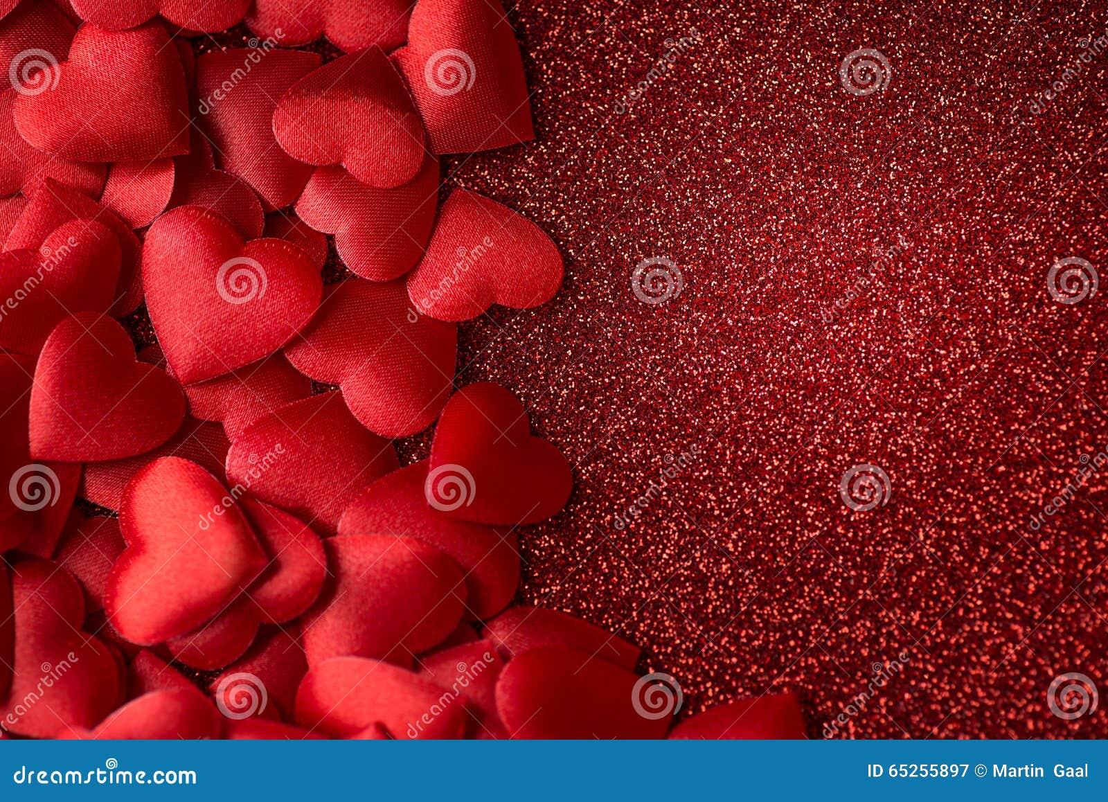 Peu de coeurs rouges de satin sur le fond rouge de jour de texture, de valentines ou de mères de scintillement