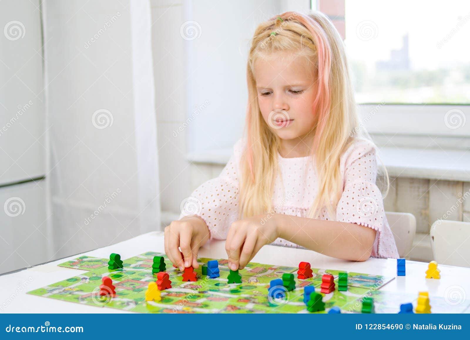 Peu de fille blonde joue - des chiffres de personnes de prise à disposition déchets de bois jaunes, bleus, verts chez le jeu des