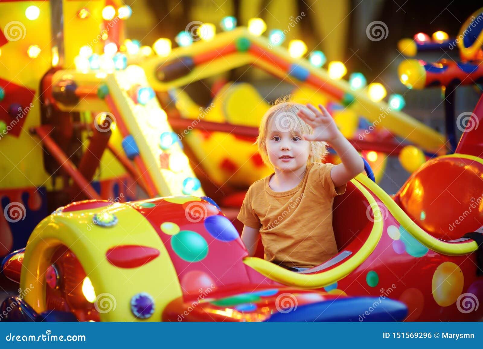 Peu de garçon ayant l amusement sur l attraction dans le parc public L équitation d enfant sur un joyeux vont rond à la soirée d