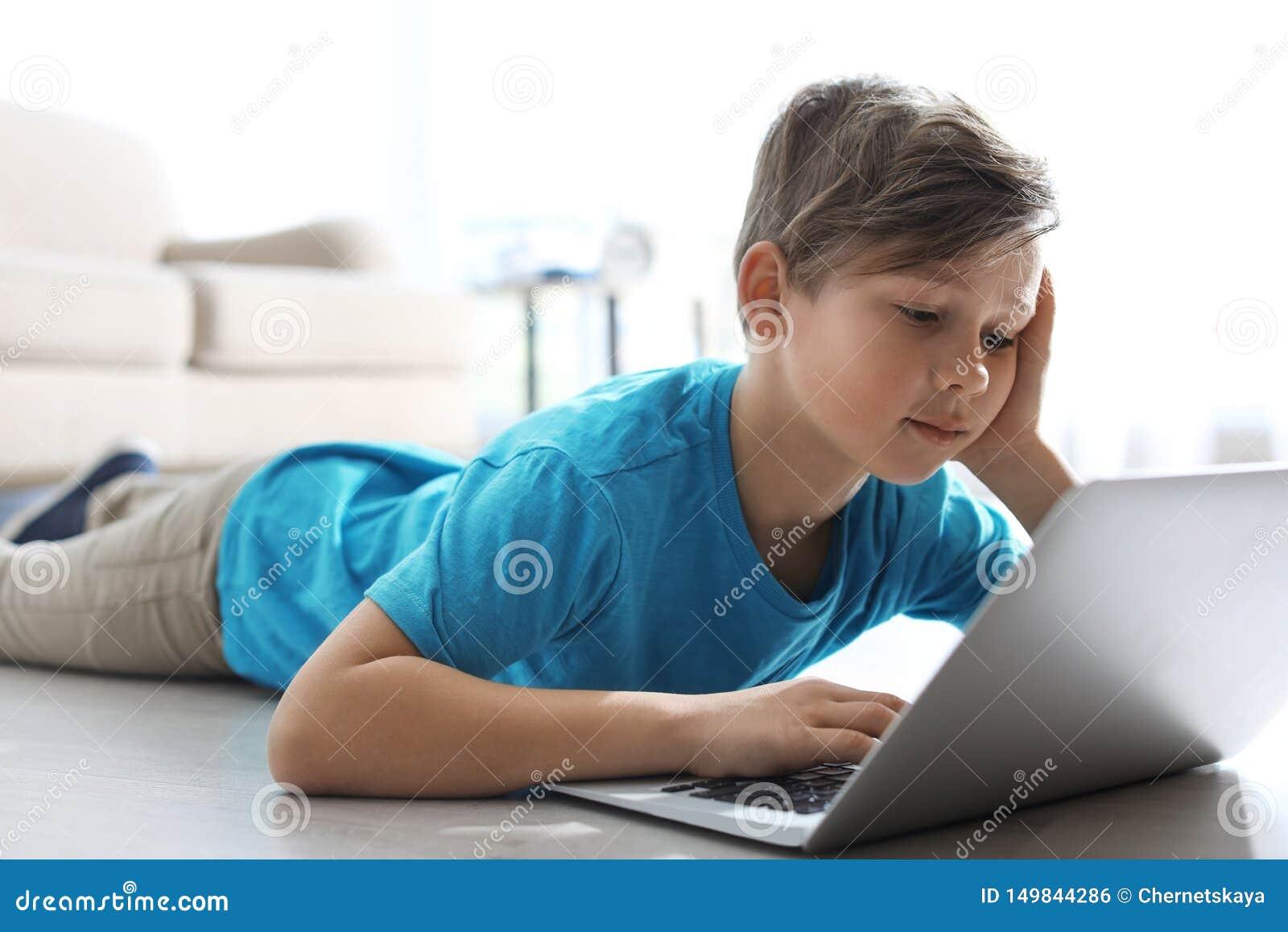 Peu enfant avec l ordinateur portable sur le plancher à l intérieur