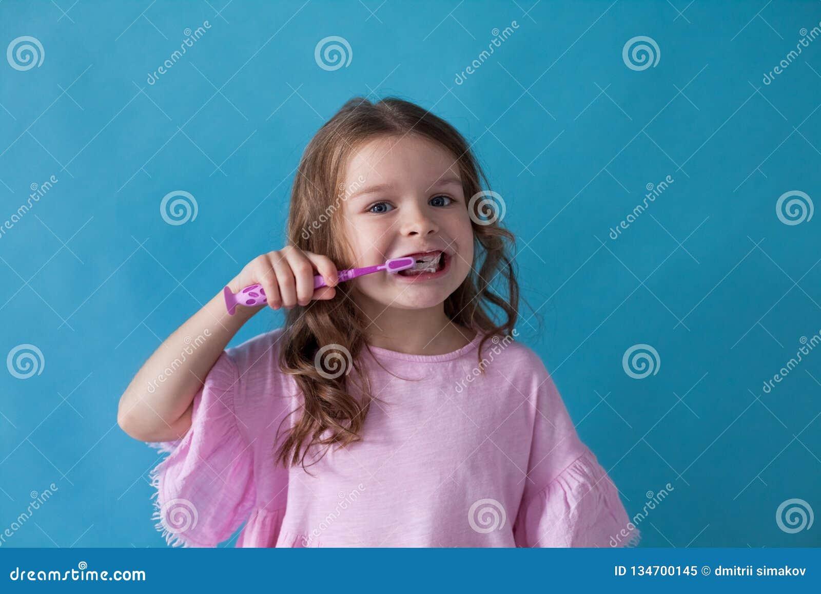 Peu fille avec une dent avec une bosselure de brosse à dents