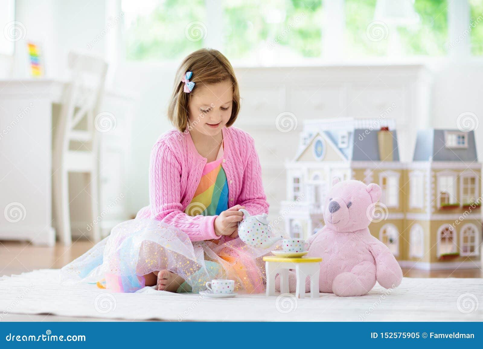 Peu fille jouant avec la maison de poupée Enfant avec des jouets