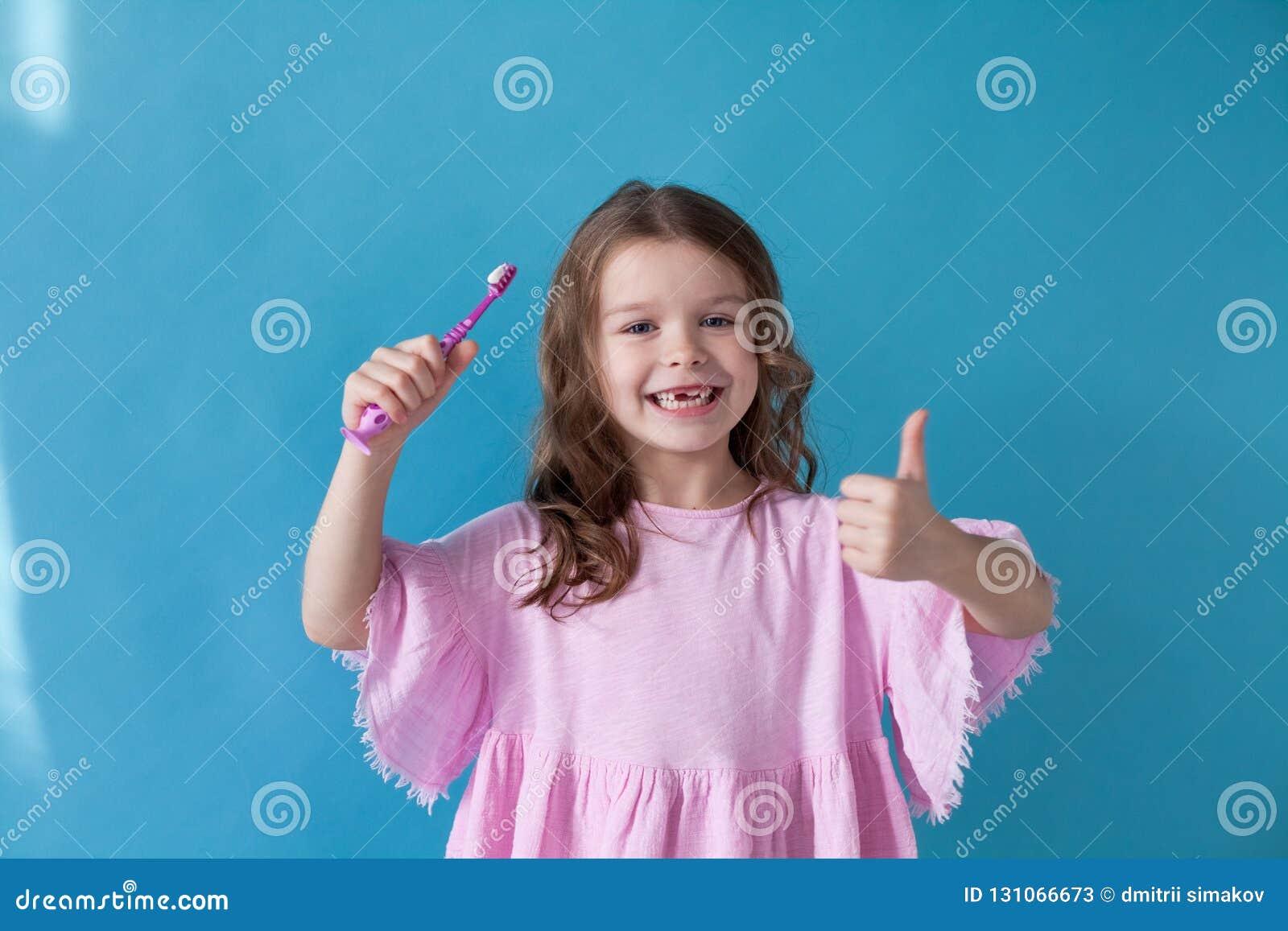 Peu fille nettoie la bosselure de brosse à dents de dents gentille