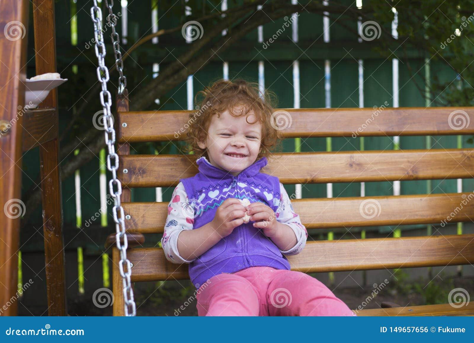 Peu fille rousse s asseyant sur un banc