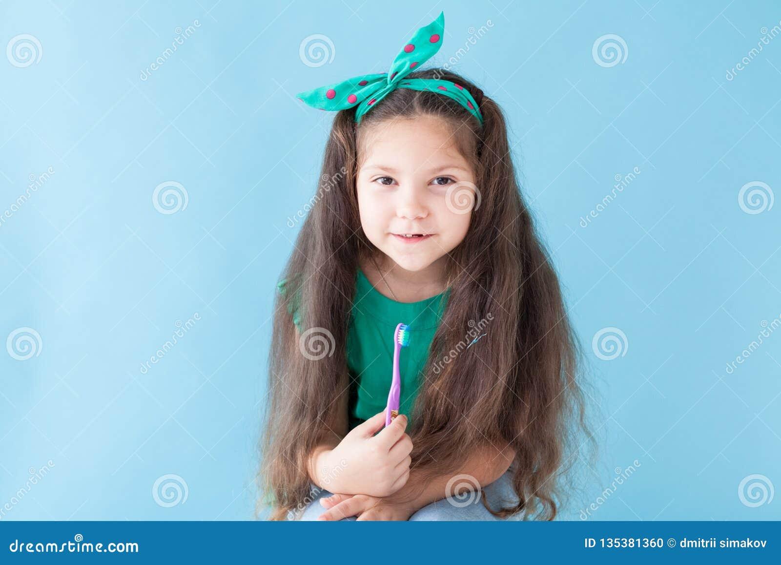 Peu fille se brossant les dents avec une bosselure de brosse à dents