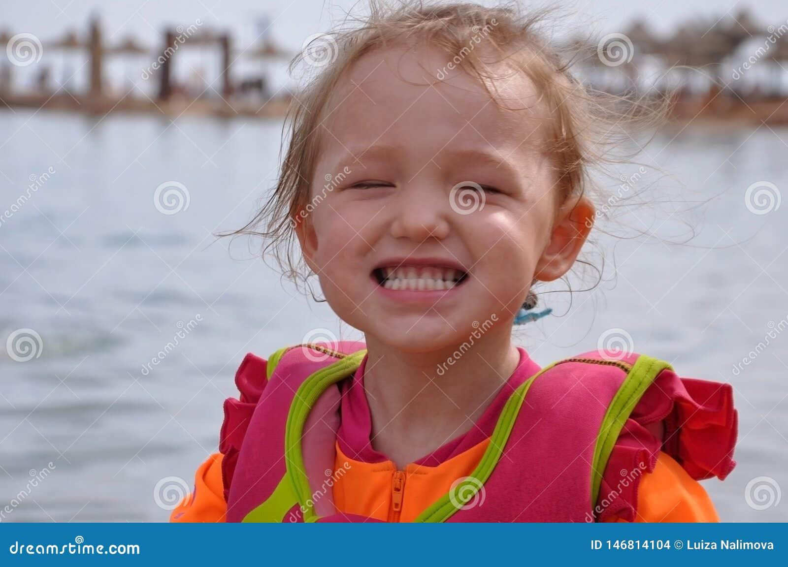 Peu fille souriant sur la plage