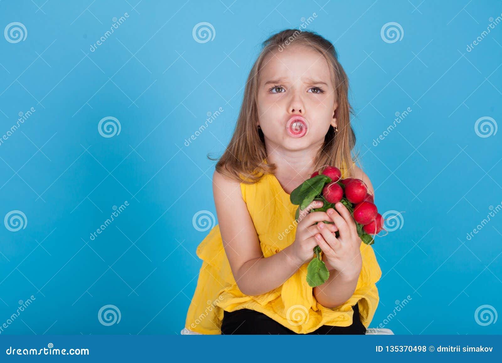 Peu fille tenant les légumes sains d un aliment de radis rouges