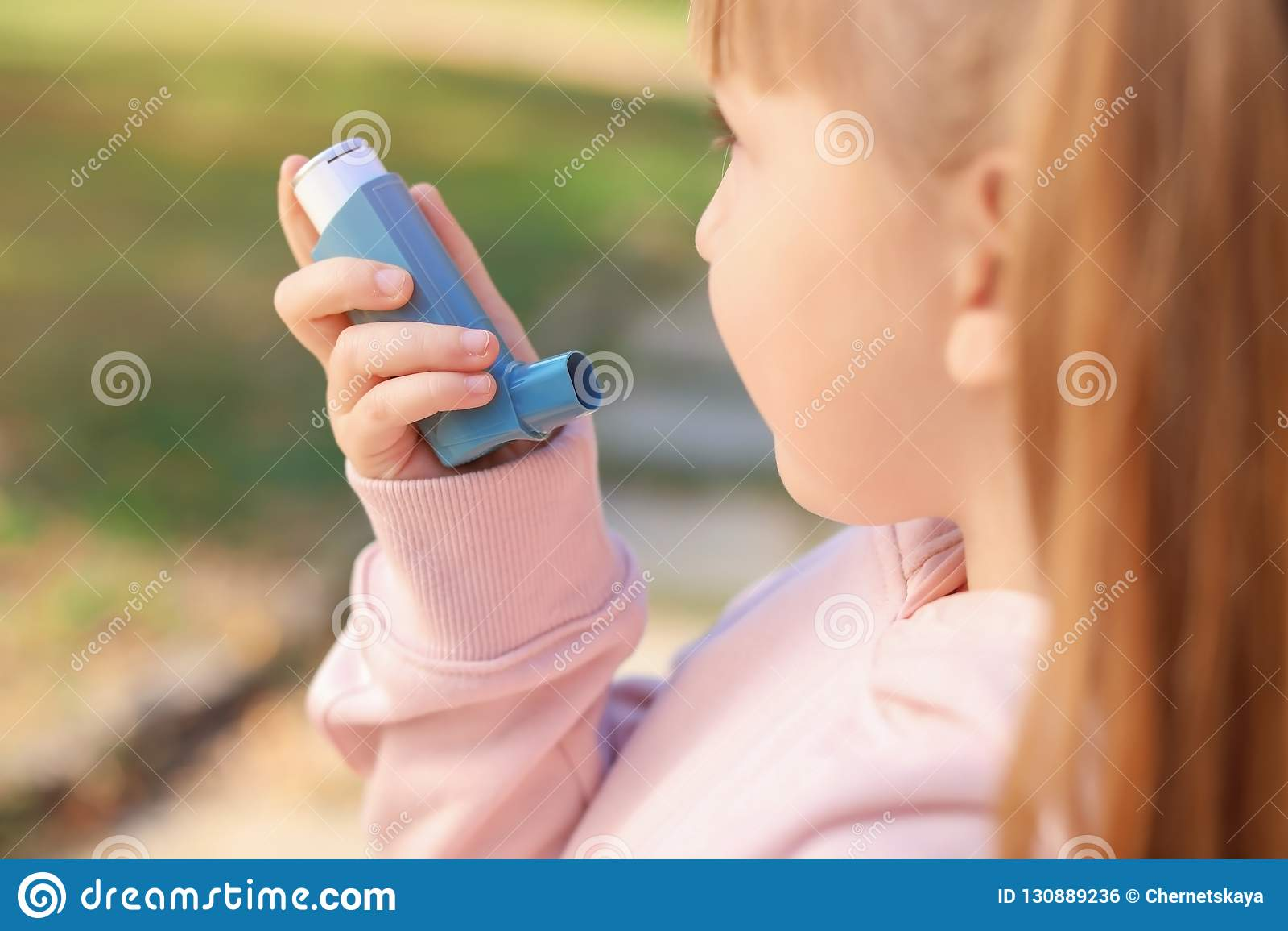 Peu fille utilisant l inhalateur d asthme dehors