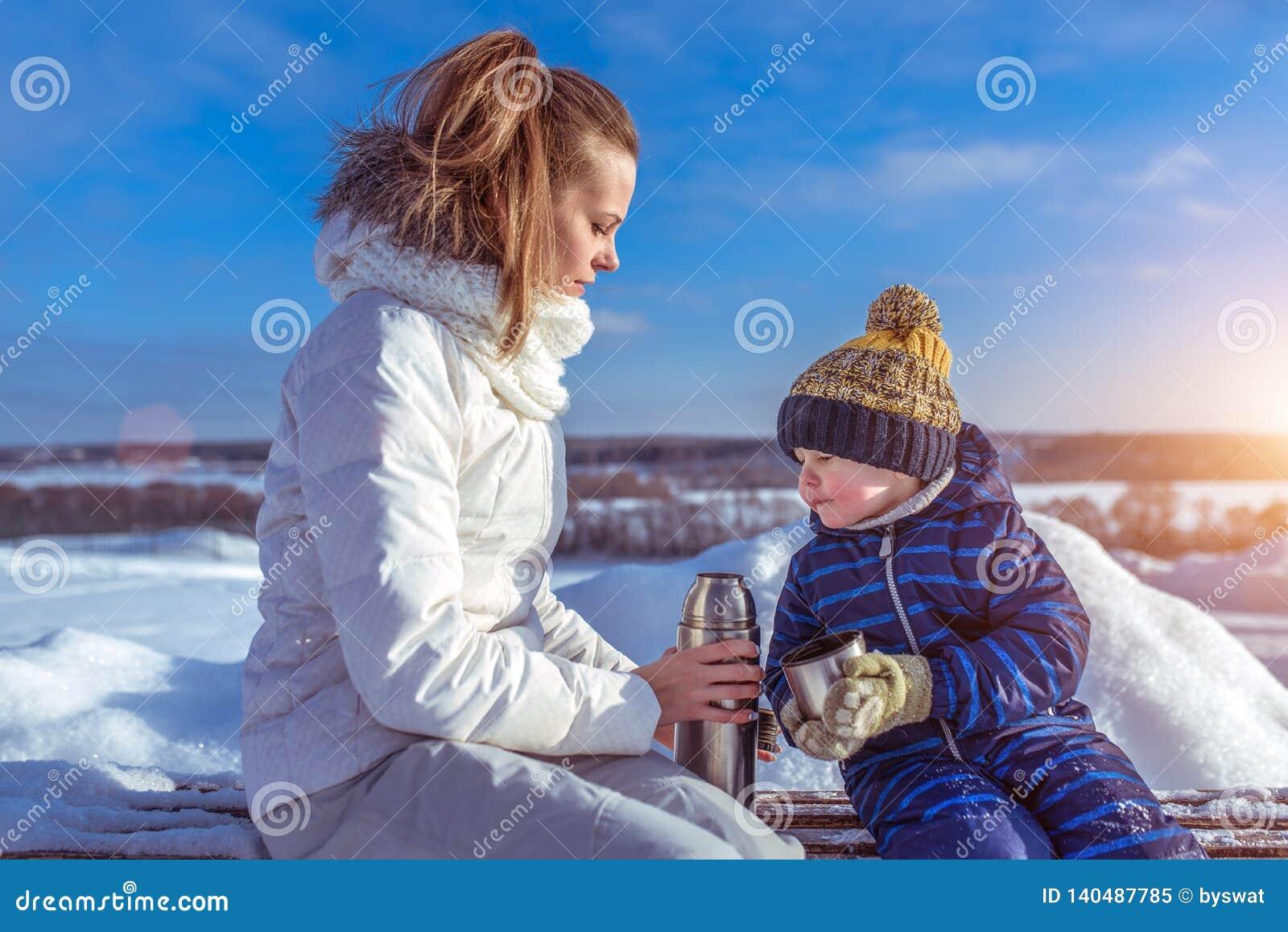 Peu fils de garçon 2 ou 3 années, se reposant l hiver de banc dans la ville Maman de femme tenant le thermos avec une boisson cha