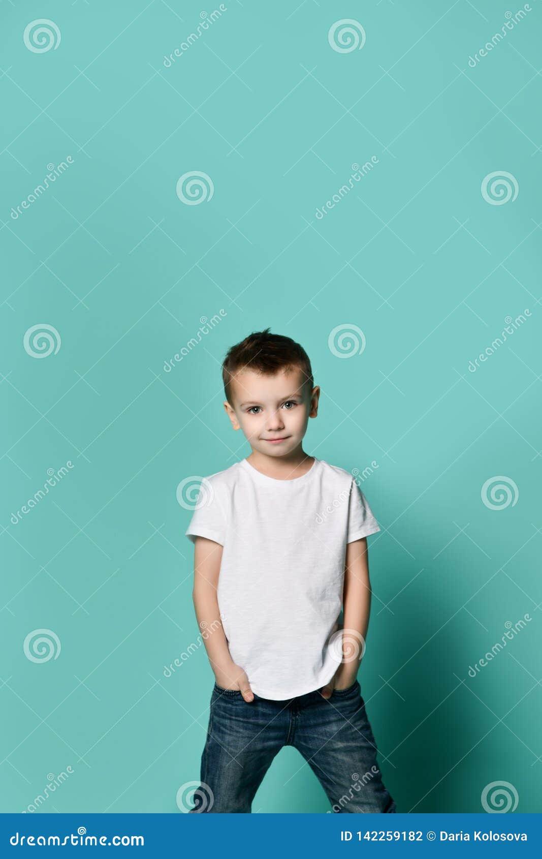 Peu garçon à la mode posant devant le mur bleu