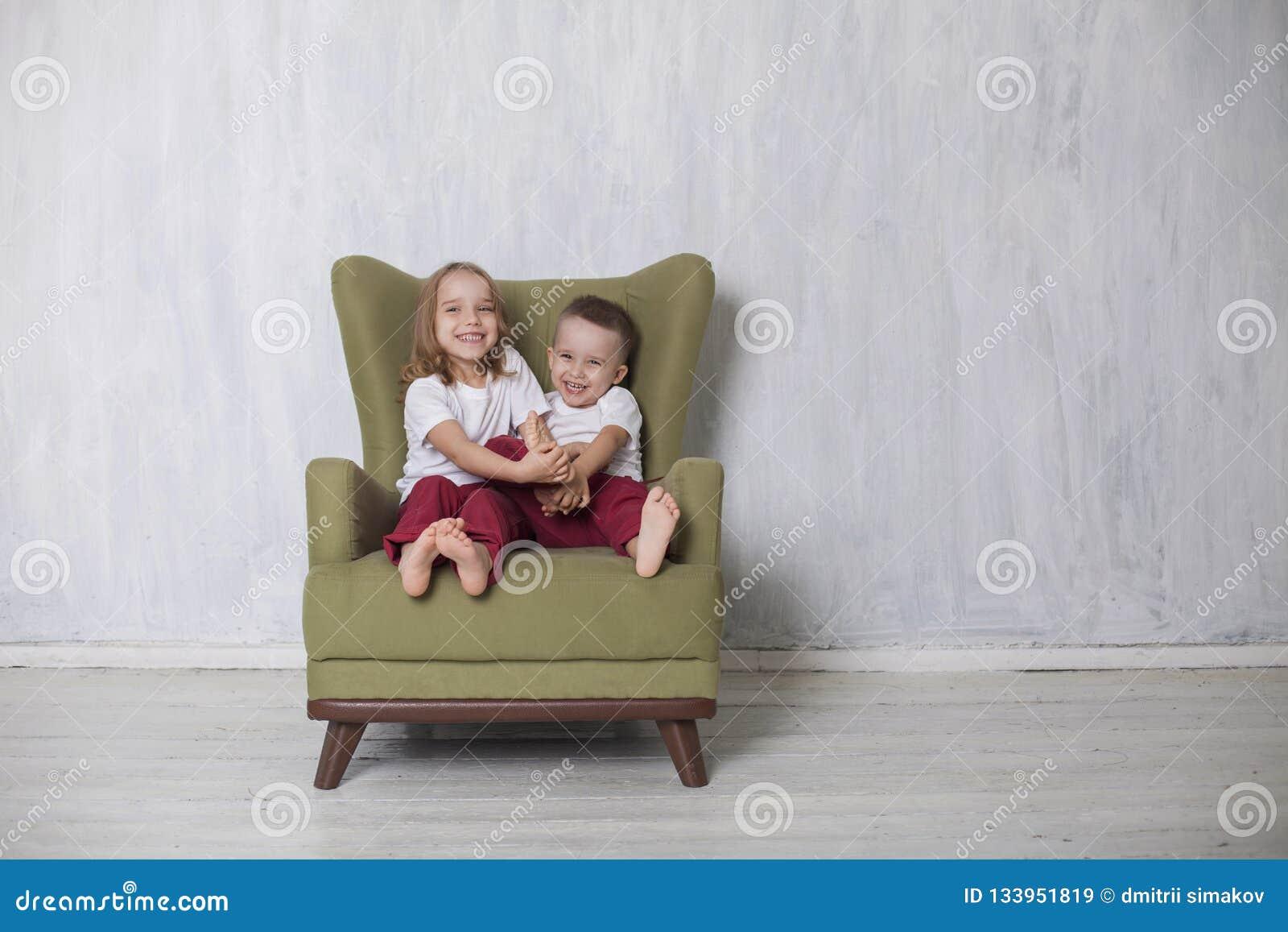 Peu garçon et fille sont frère et la soeur s asseyent sur une chaise verte
