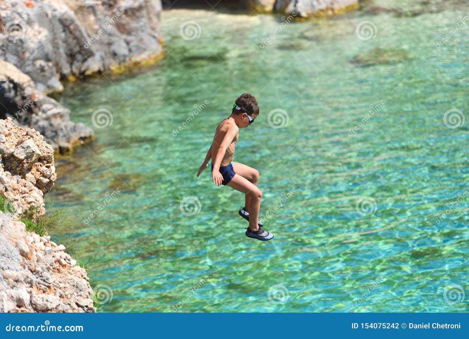 Peu garçon sautant outre de la falaise dans l océan Mode de vie d amusement d ?t? Gosse courageux