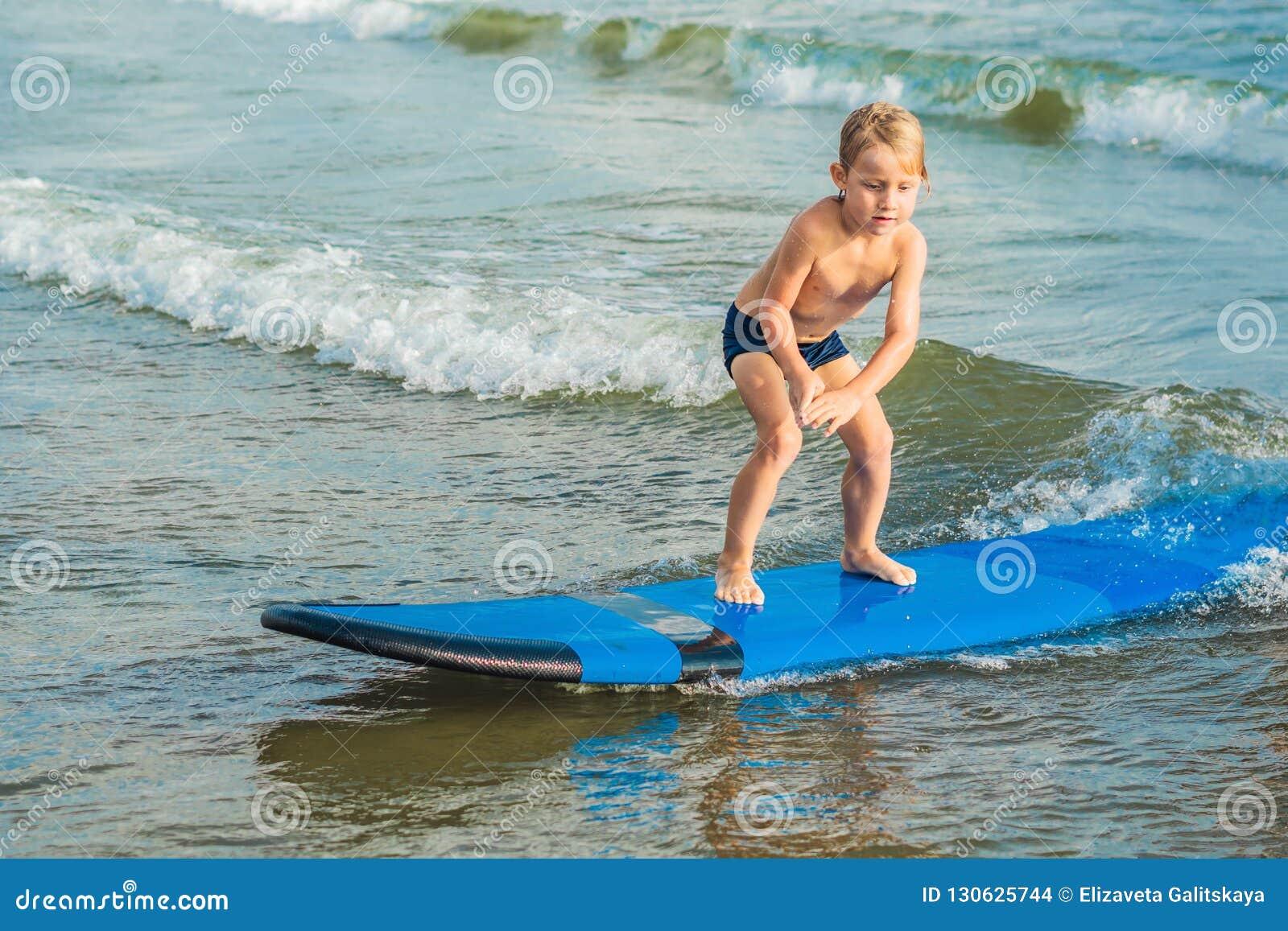 Peu garçon surfant sur la plage tropicale Enfant sur le panneau de ressac sur le ressac Sports aquatiques actifs pour des enfants