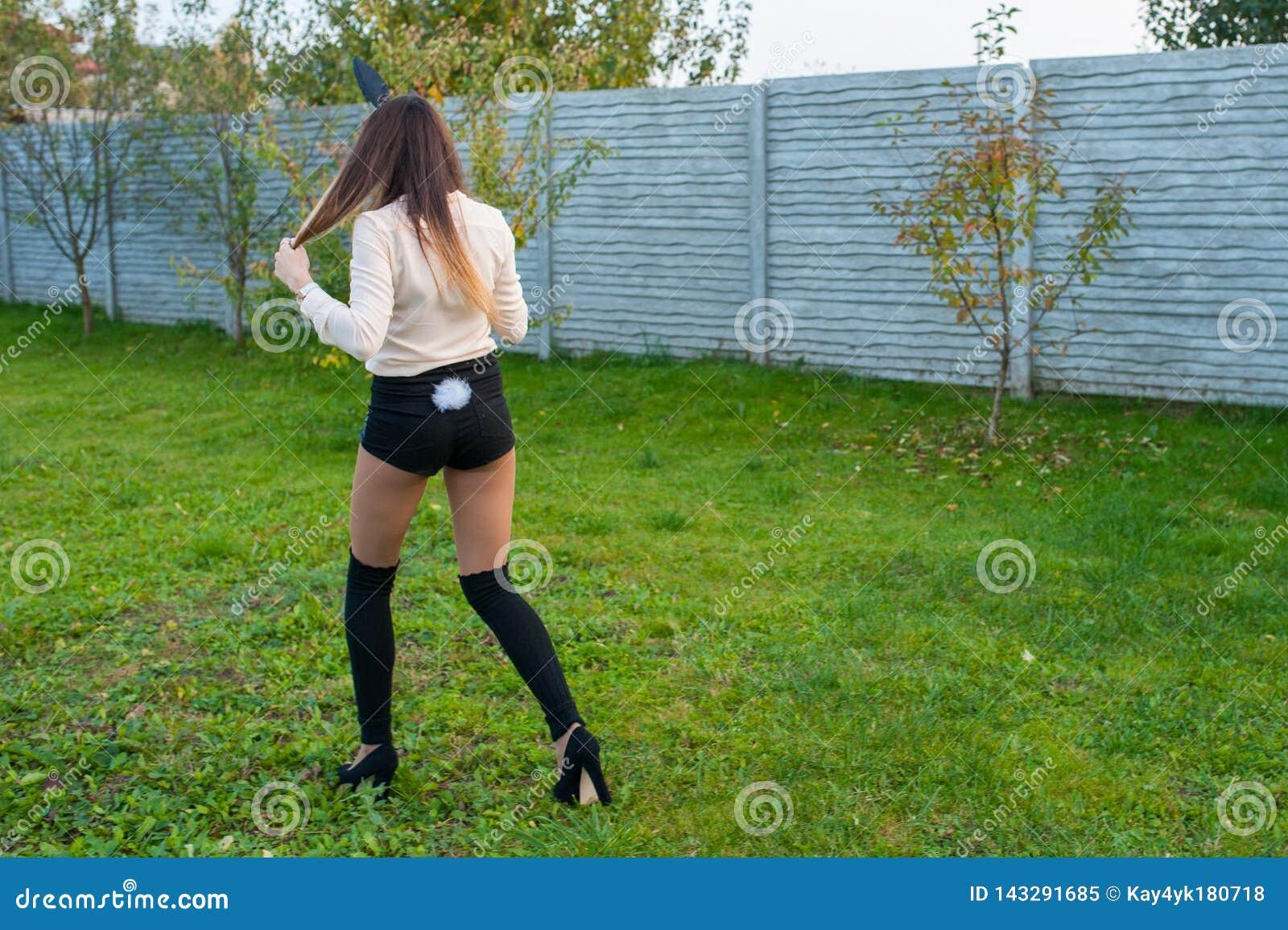 Peu jolie fille avec des oreilles de lièvres se repose sur l herbe et tient le panier avec les oeufs colorés au jour nuageux