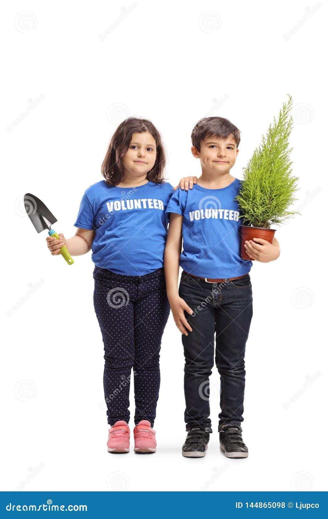 Peu volontaires de garçon et de fille tenant une usine et une pelle