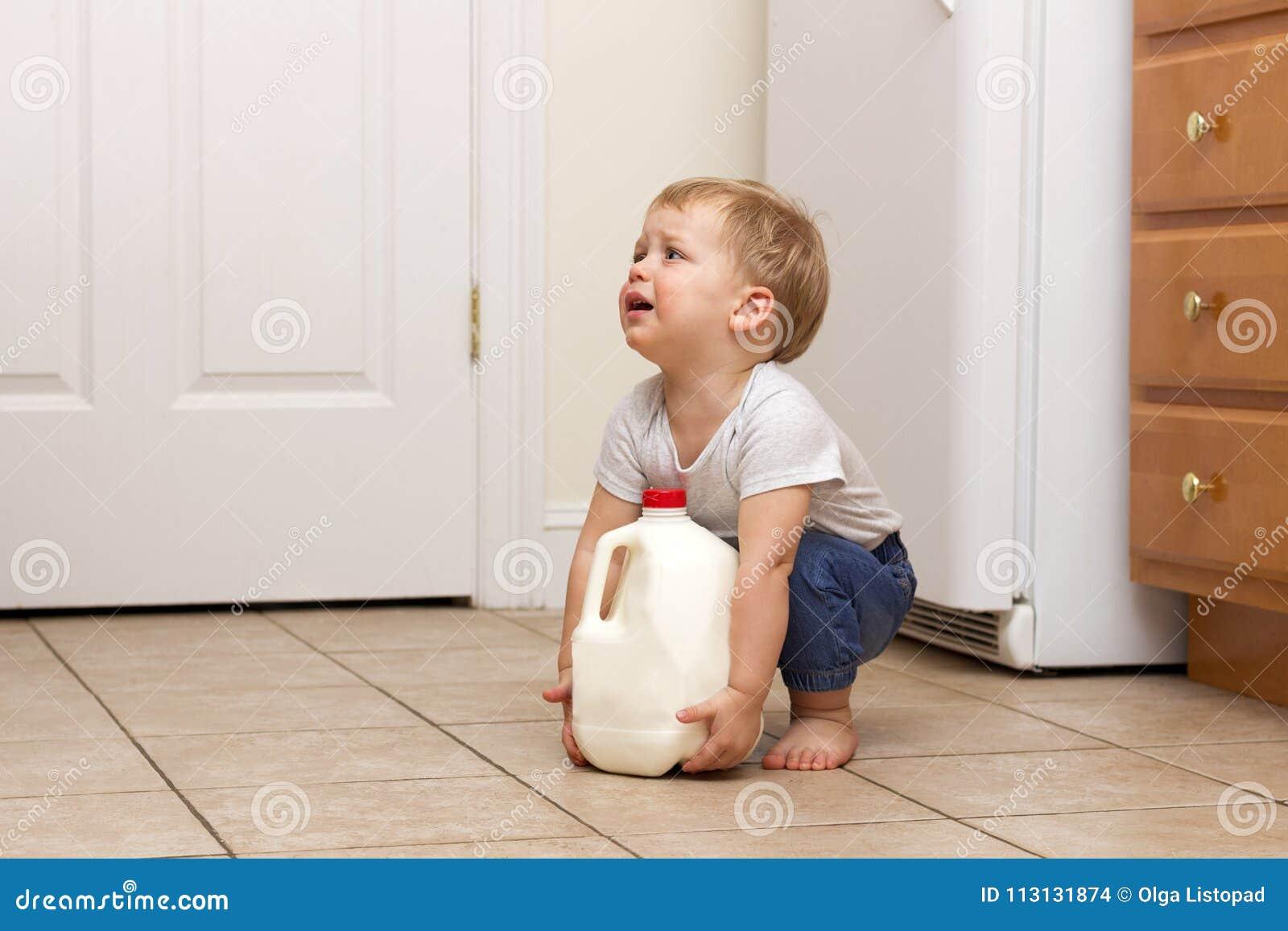 Peuter die gallon melk proberen op te heffen De ruimte van het exemplaar