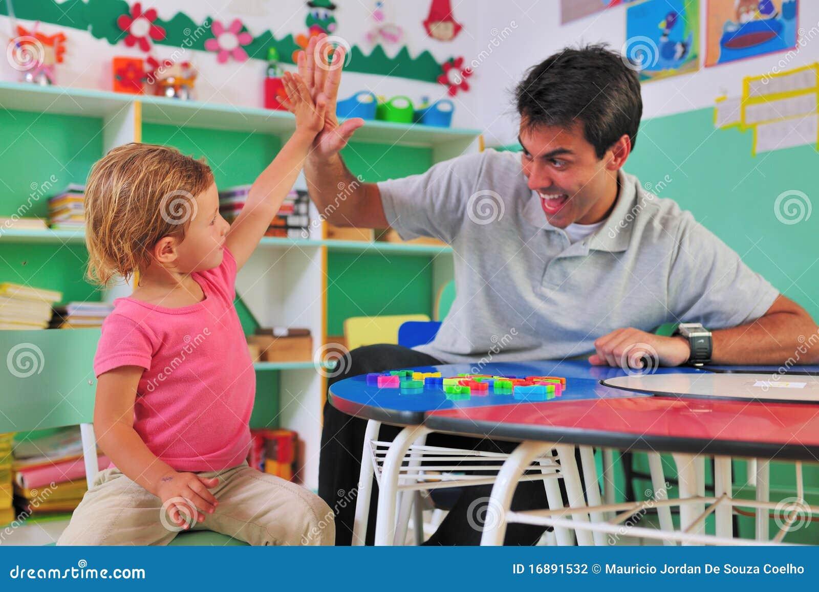 Peuter leraar en kind die hoog-vijf geven