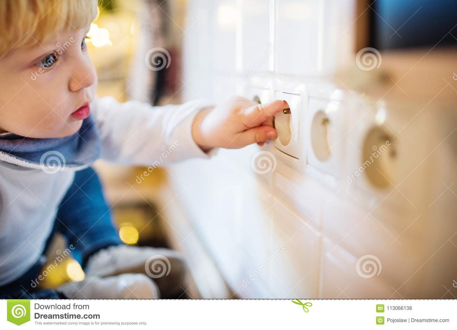 Peuterjongen in gevaarlijke situatie thuis Het concept van de kindveiligheid