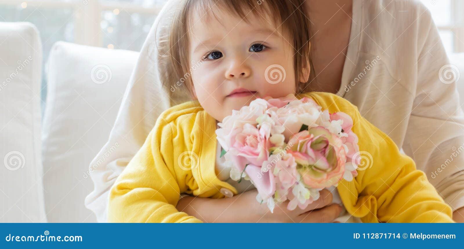 Peuterjongen met zijn bloemen van de moederholding