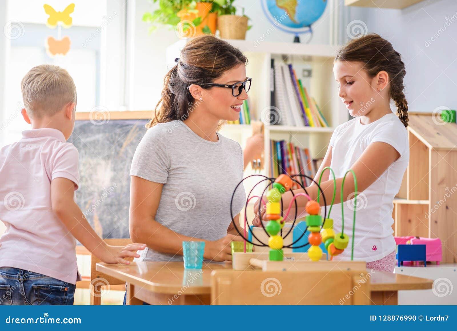 Peuterleraar met kinderen die met kleurrijk didactisch speelgoed bij kleuterschool spelen