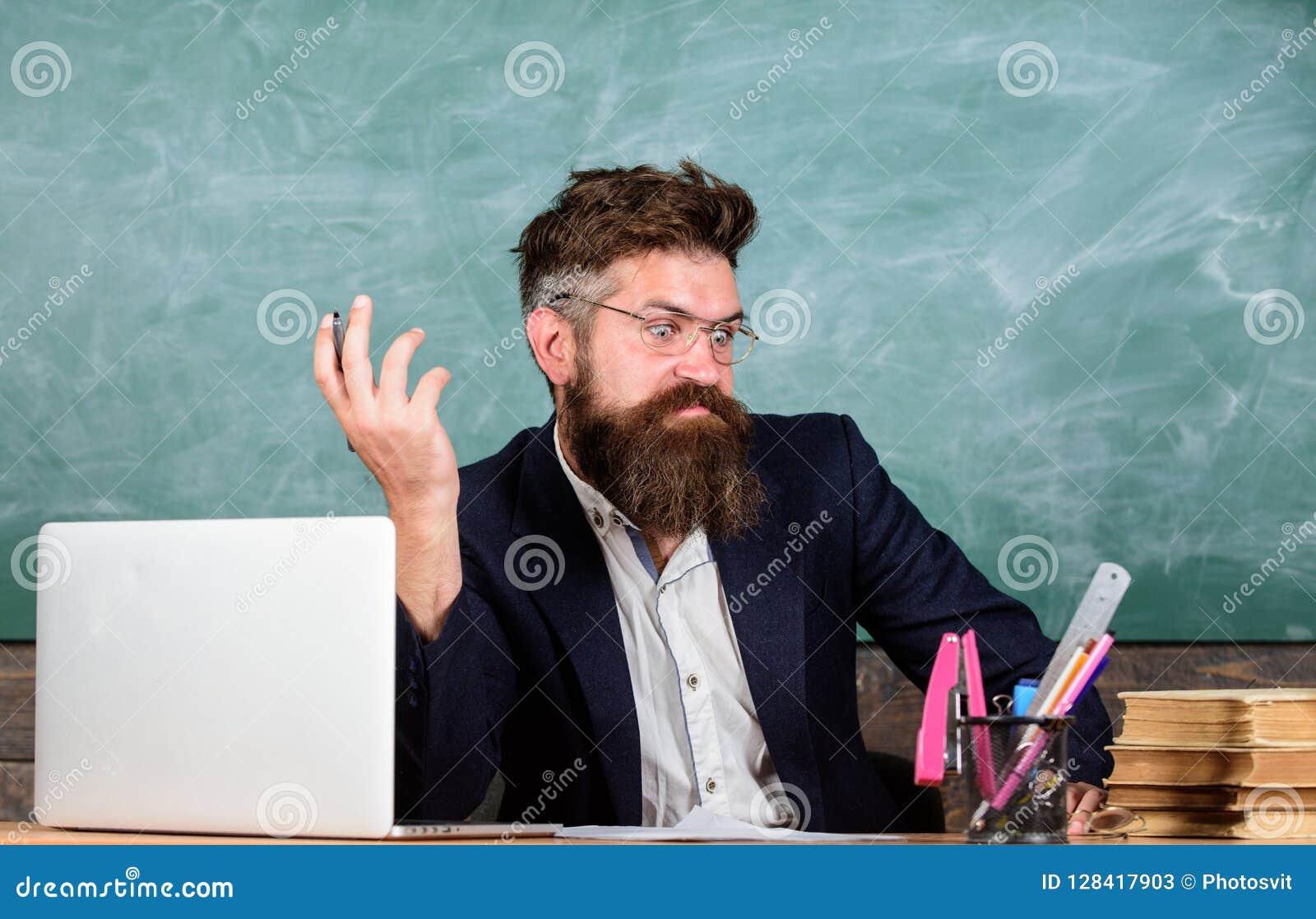 Pewny w wiedzie Egzaminator wątpienia pełno siedzi przy stołowym chalkboard tłem Chytry examinator ono waha się wokoło