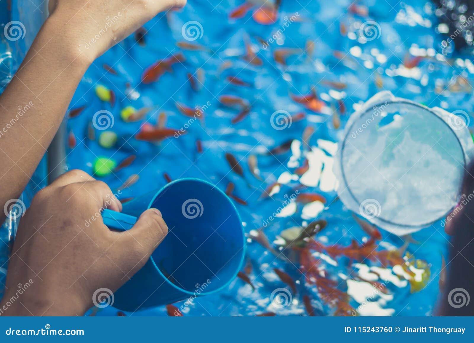 Pez de colores que saca con pala con los niños en festival anual